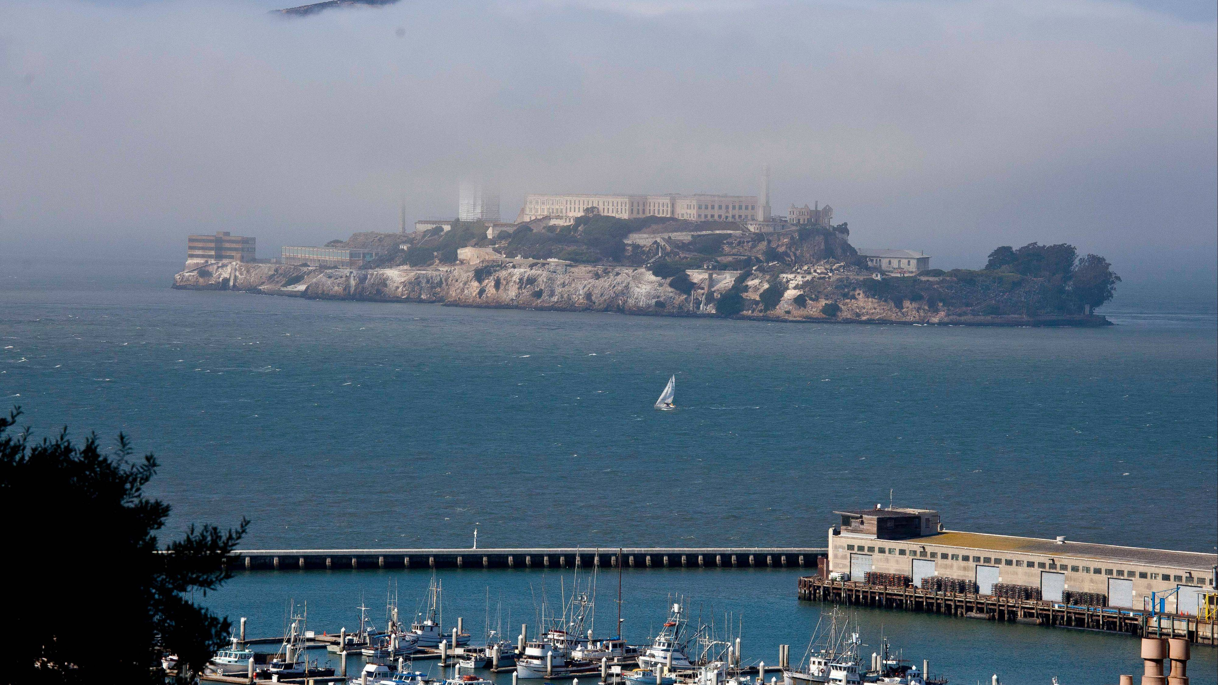 A sailboat makes its way past Alcatraz Island in San Francisco.