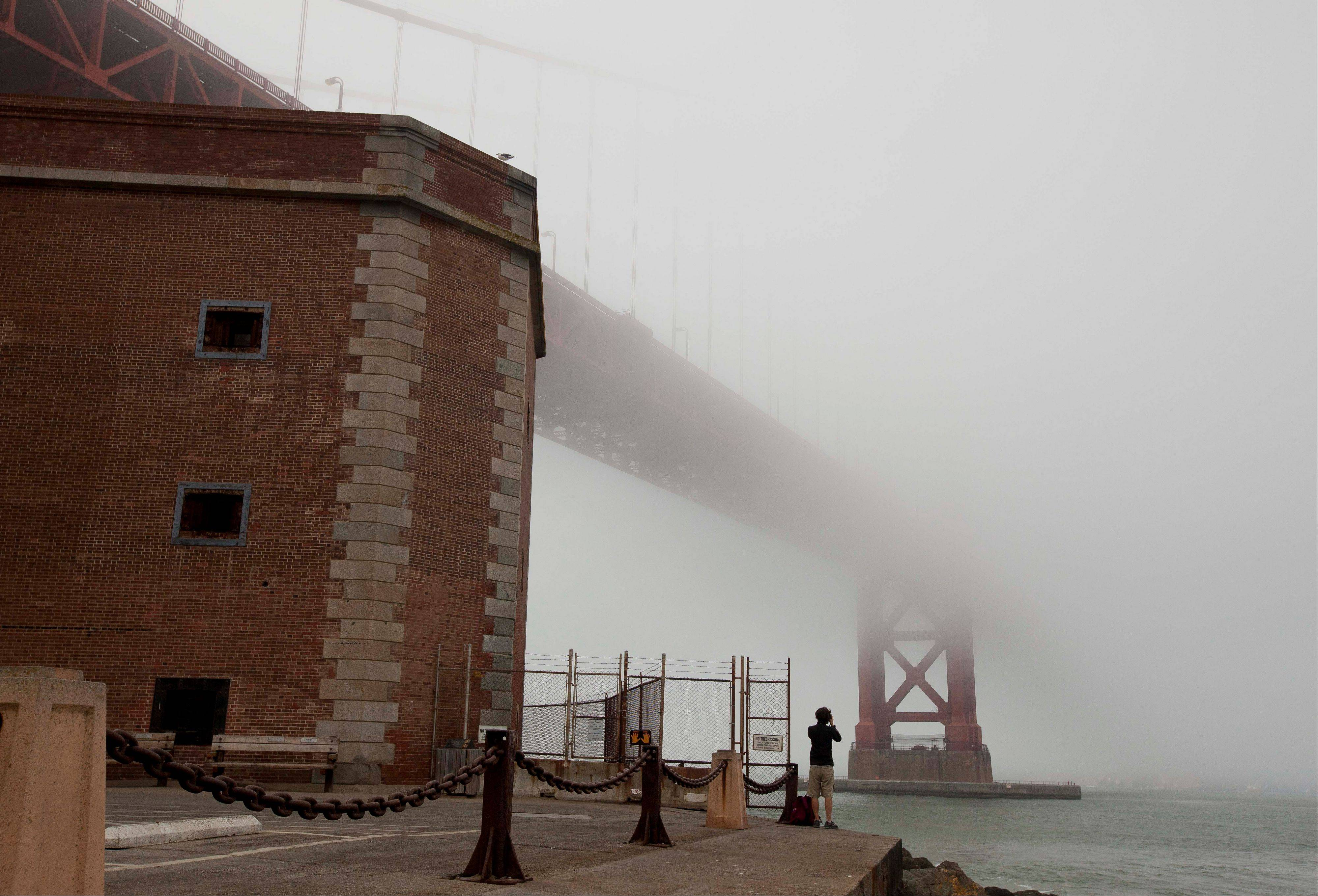 A man stands beside Fort Point and looks out at the fog-covered Golden Gate Bridge in San Francisco.
