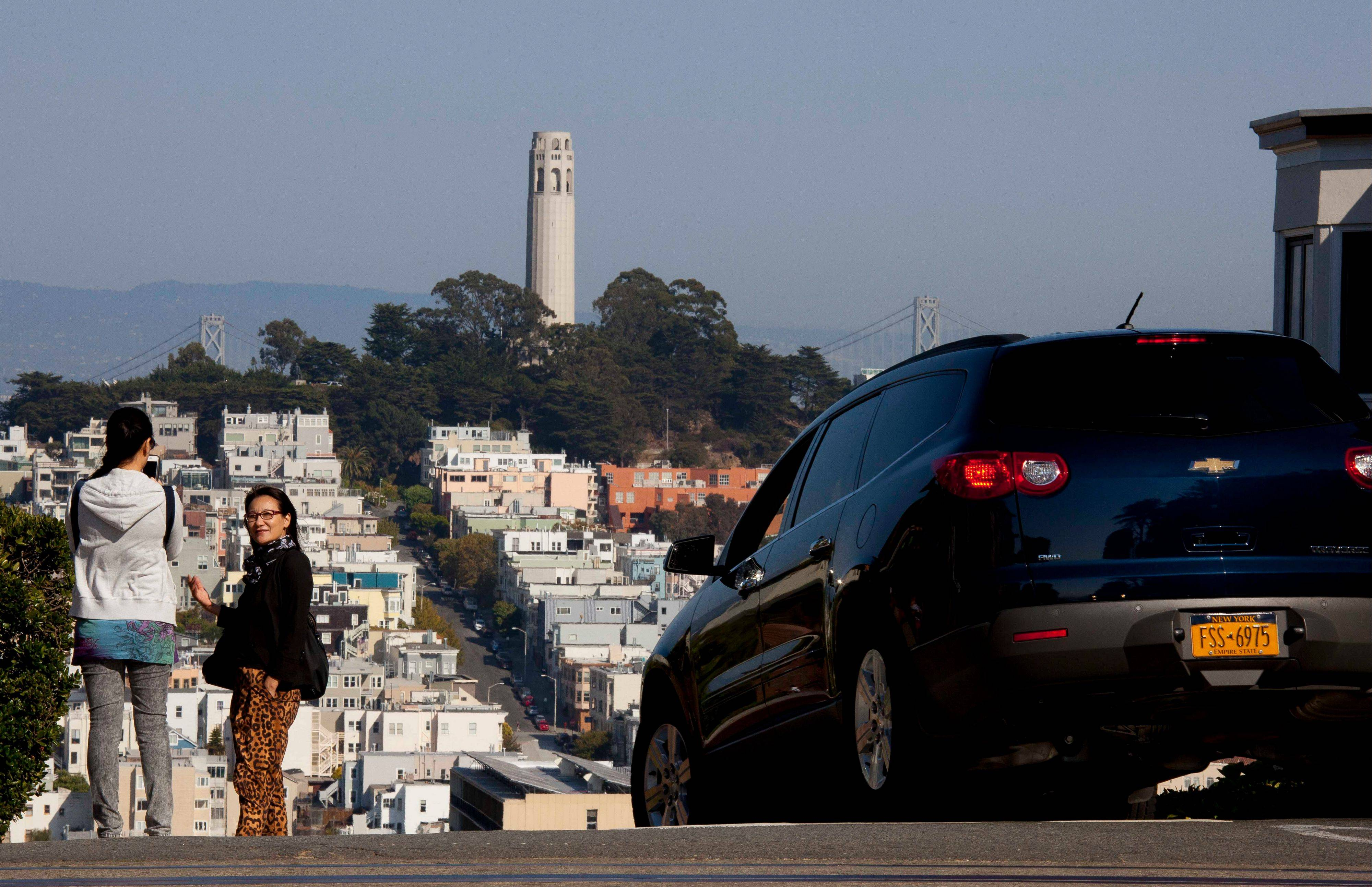 People pose for pictures and a car makes its way down Lombard Street with Coit Tower on Telegraph Hill in the background in San Francisco. The city has a long history as a favorite site for filmmakers and the movie buffs who want to see the spots where their favorite scenes took place.