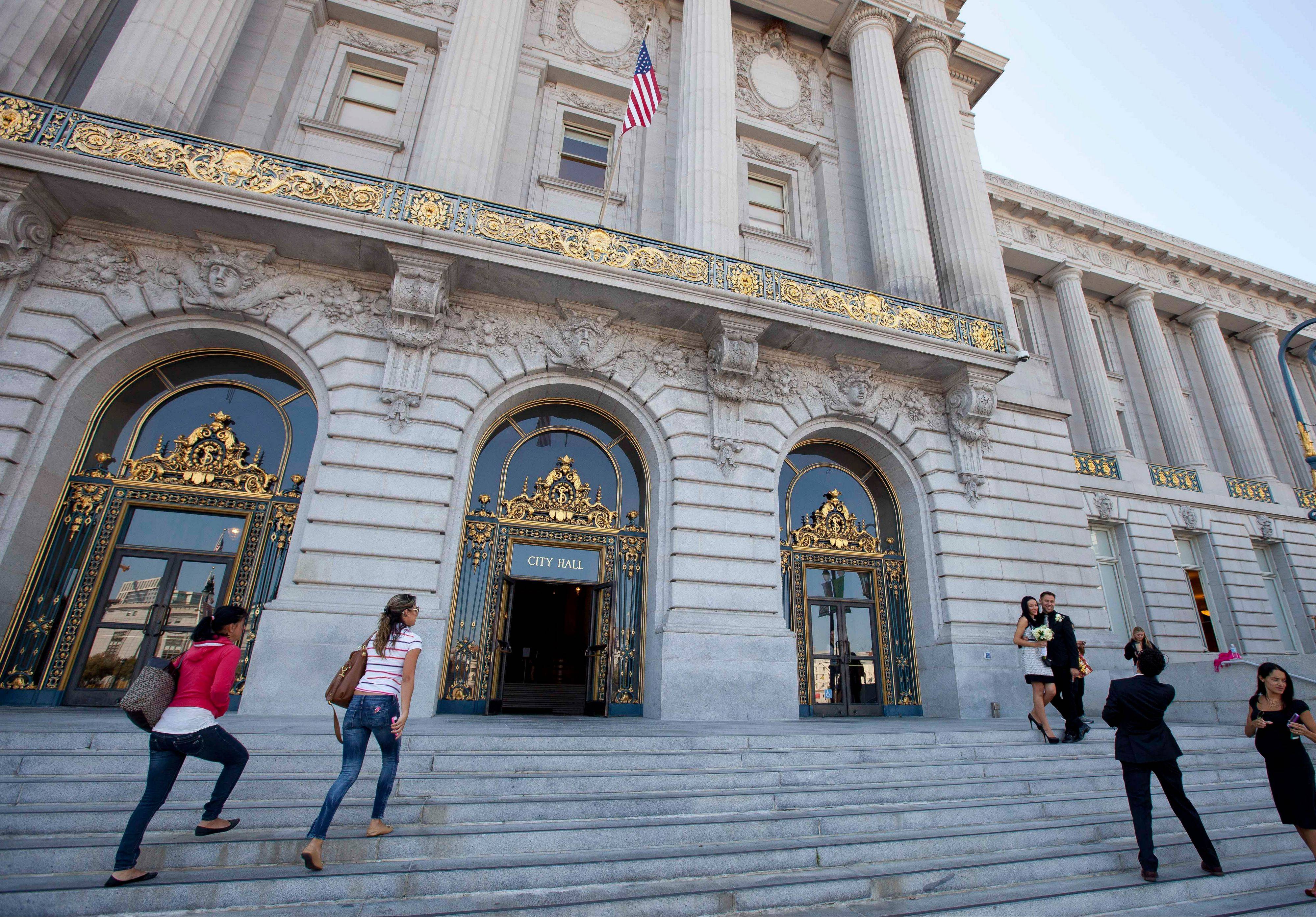 "Tourists pose for pictures and make their way up the steps to City Hall in San Francisco. On the steps of City Hall, Sean Penn gave an impassioned speech in the film ""Milk."""