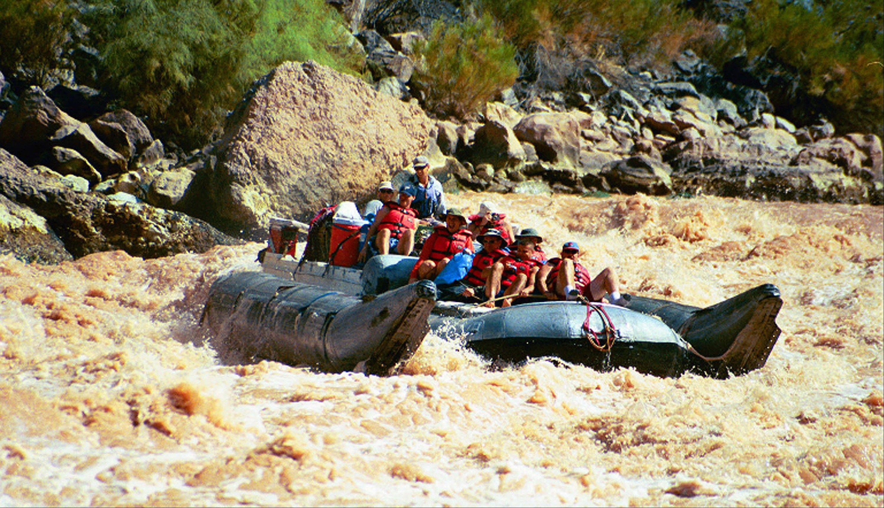 A group of visitors rides a pontoon raft through rapids in Grand Canyon National Park in Arizona. Thousands of people who had been on a waiting list for a coveted trip on the Colorado River through the Grand Canyon still are waiting.