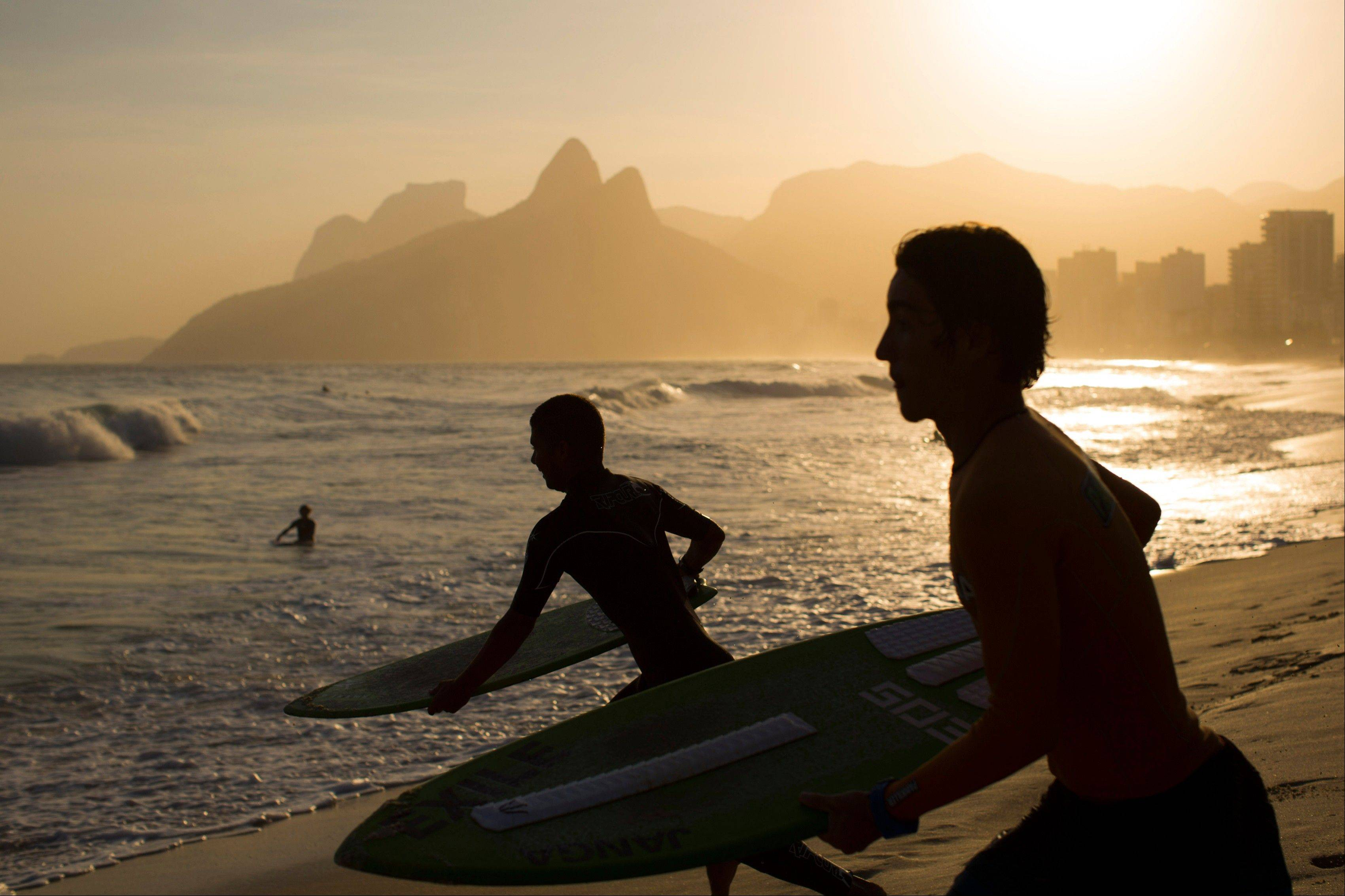 Skimboarders run to the water at Ipanema beach.