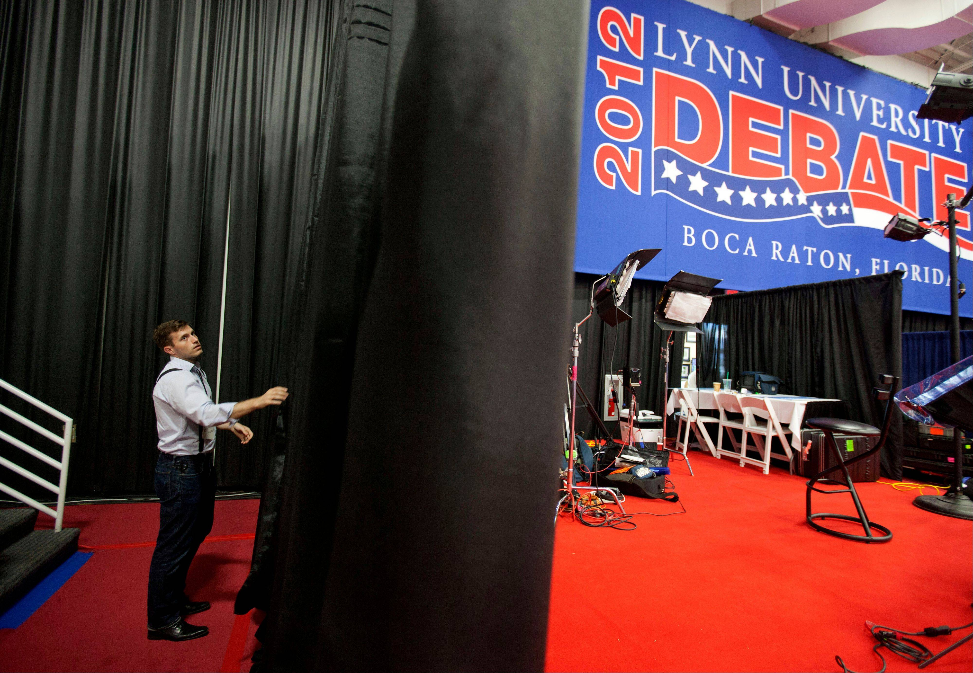 A campaign worker works on the set for the spin corner for the President Barack Obama campaign in the media center ahead of Monday's presidential debate between Republican presidential candidate, former Massachusetts Gov. Mitt Romney and Obama, Sunday at Lynn University in Boca Raton, Fla.