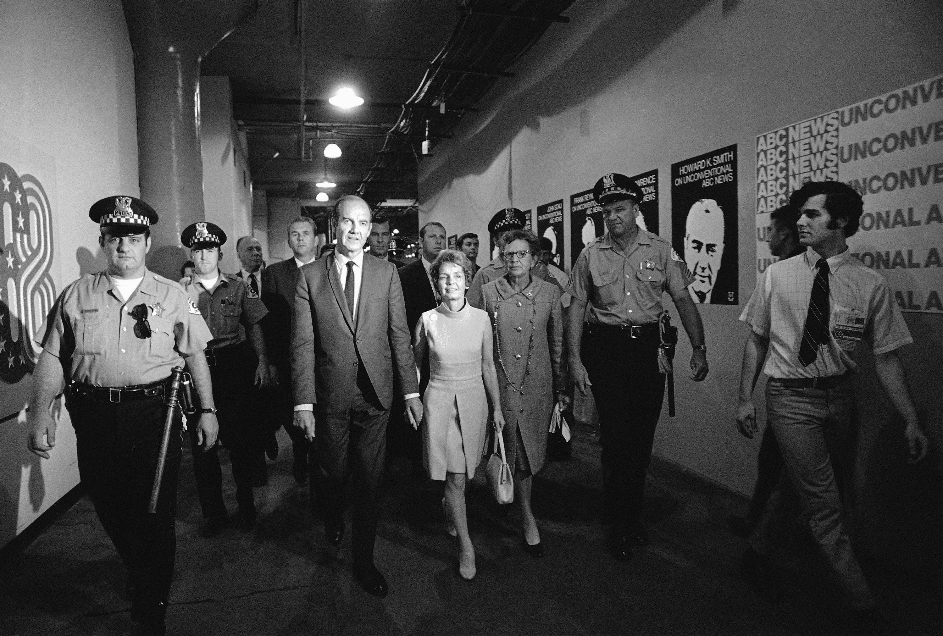 A phalanx of policemen and Secret Service agents accompanies Sen. George McGovern and his wife as they leave International Amphitheatre in Chicago, August 25, 1968, following an appearance by the candidate for the Democratic presidential nomination on a television show.