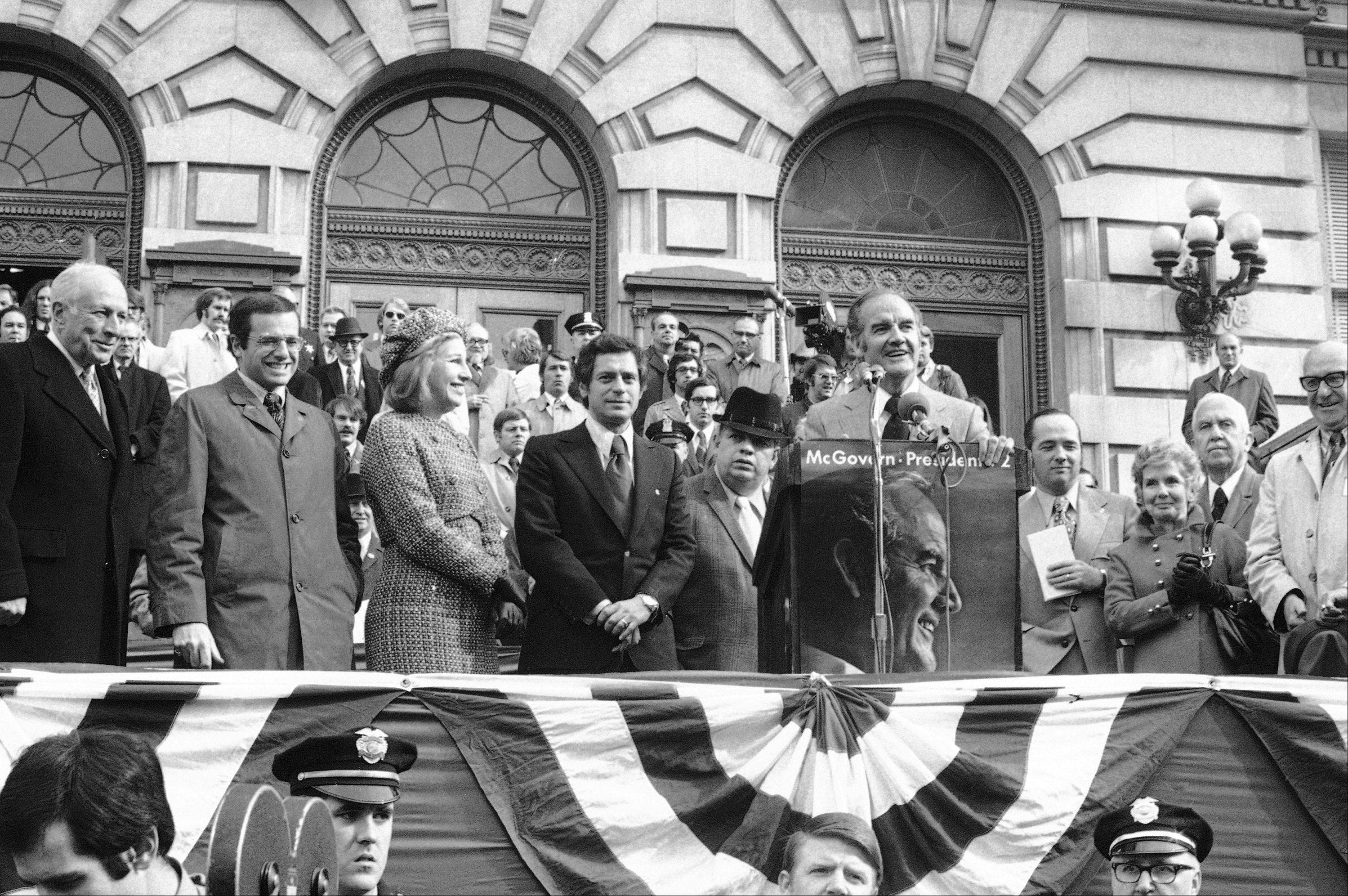 Senator George McGovern made a campaign stop in downtown Syracuse, Oct. 31, 1972, and was accompanied by mayors from many cities in the state. From left: Mayor Erastus Corning of Albany, Mayor Alfred Del Bello of Yonkers; Mrs. And Mr. Alexander of Syracuse, Senator McGovern at podium, Joseph Crangle, state chairman, Mrs. and Mayor Frank Sedita of Buffalo.