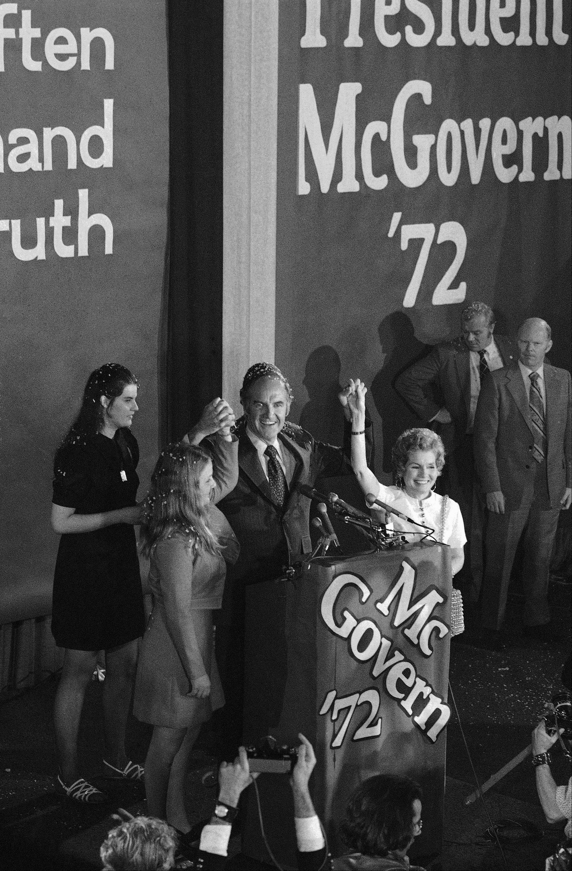 Sen. George McGovern holds up hands of his wife Eleanor and Daughter Teresa, left, to cheers of supporters in Midtown Manhattan Hotel, Tuesday, June 20, 1972 as he claimed victory in the New York democratic presidential primary.
