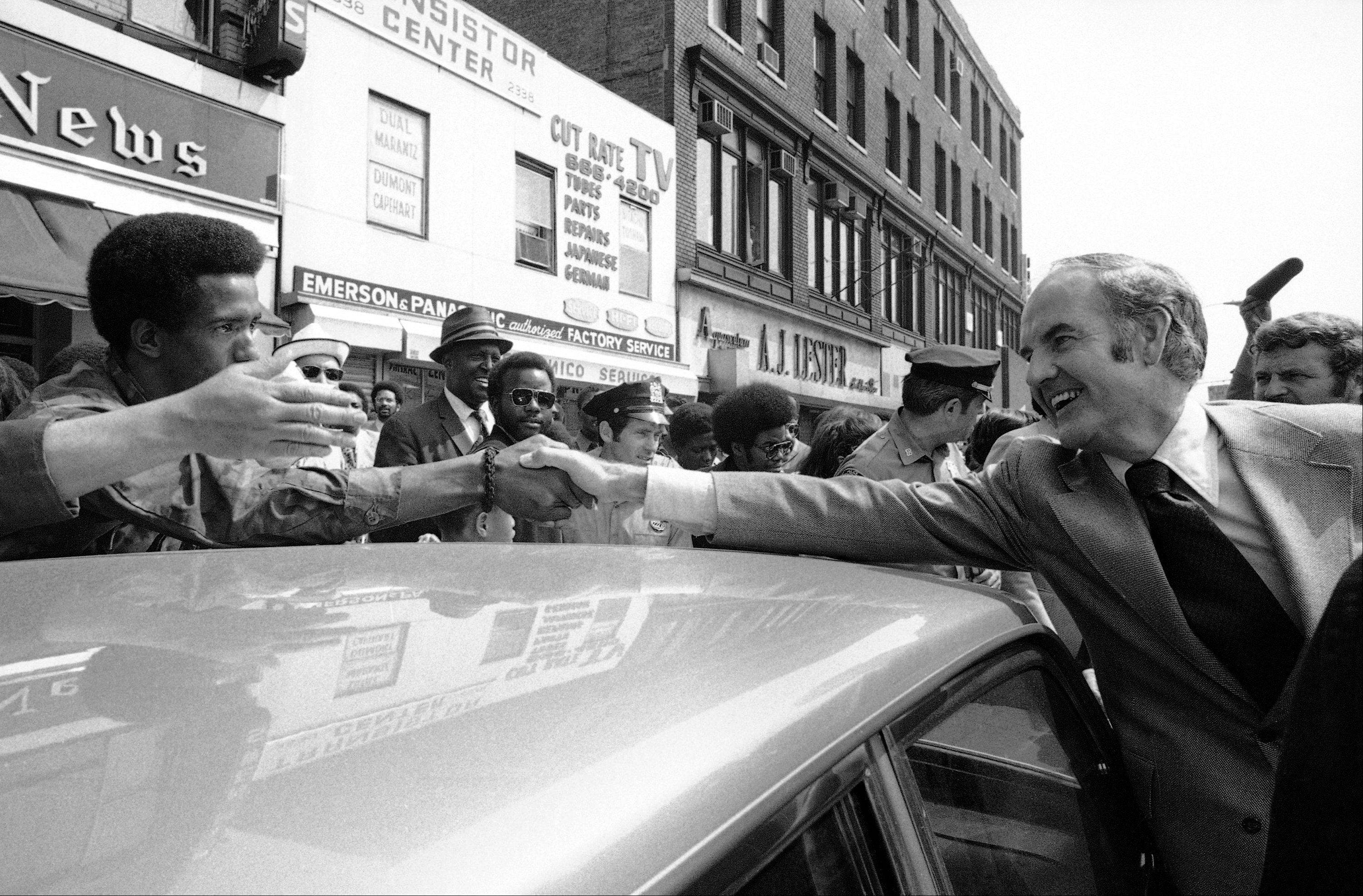 Sen. George McGovern and a New Yorker reach over a car to shake hands, during a visit by McGovern to Harlem in New York, June 9, 1972. McGovern, who is a candidate for the Democratic presidential nomination, was in Harlem to speak to editors of the Amsterdam News, a black-run newspaper.