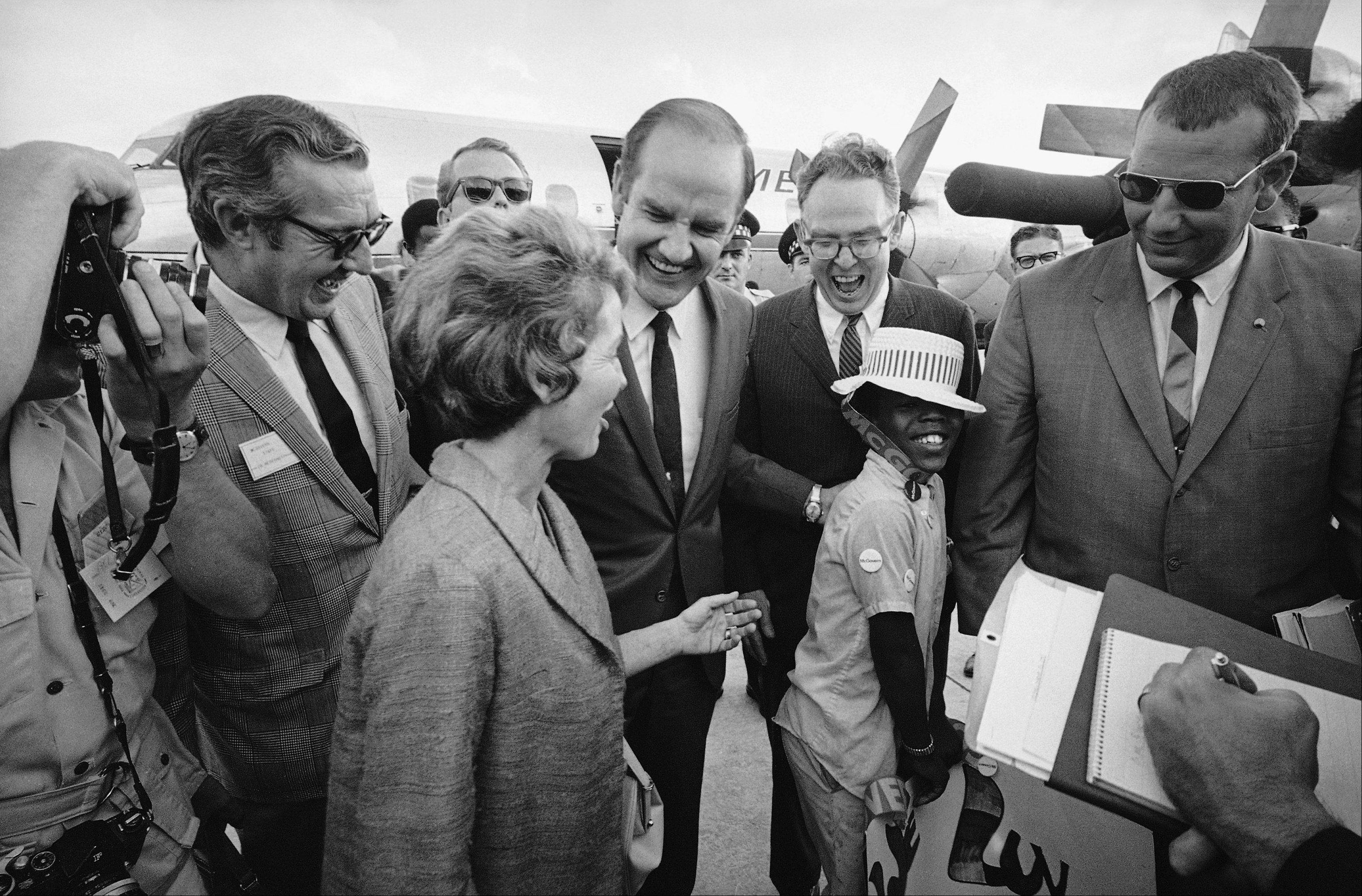 Sen. and Mrs. George S. McGovern of South Dakota, and an aid enjoy a good laugh after remark by Duane Calhoun, II, of Chicago who greeted them on arrival at Midway Airport in Chicago, Friday, August 23, 1968.