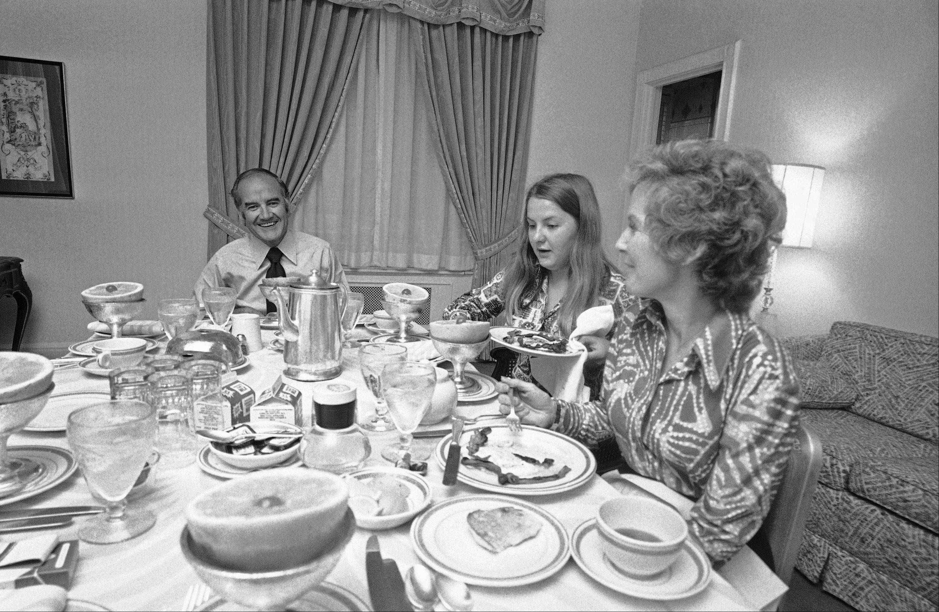 Sen. George McGovern, Democratic presidential candidate, has breakfast with his daughter Terry, center, and his wife Eleanor, Wednesday, June 21, 1972, at his hotel Biltmore headquarters in New York following primary victory in New York State.
