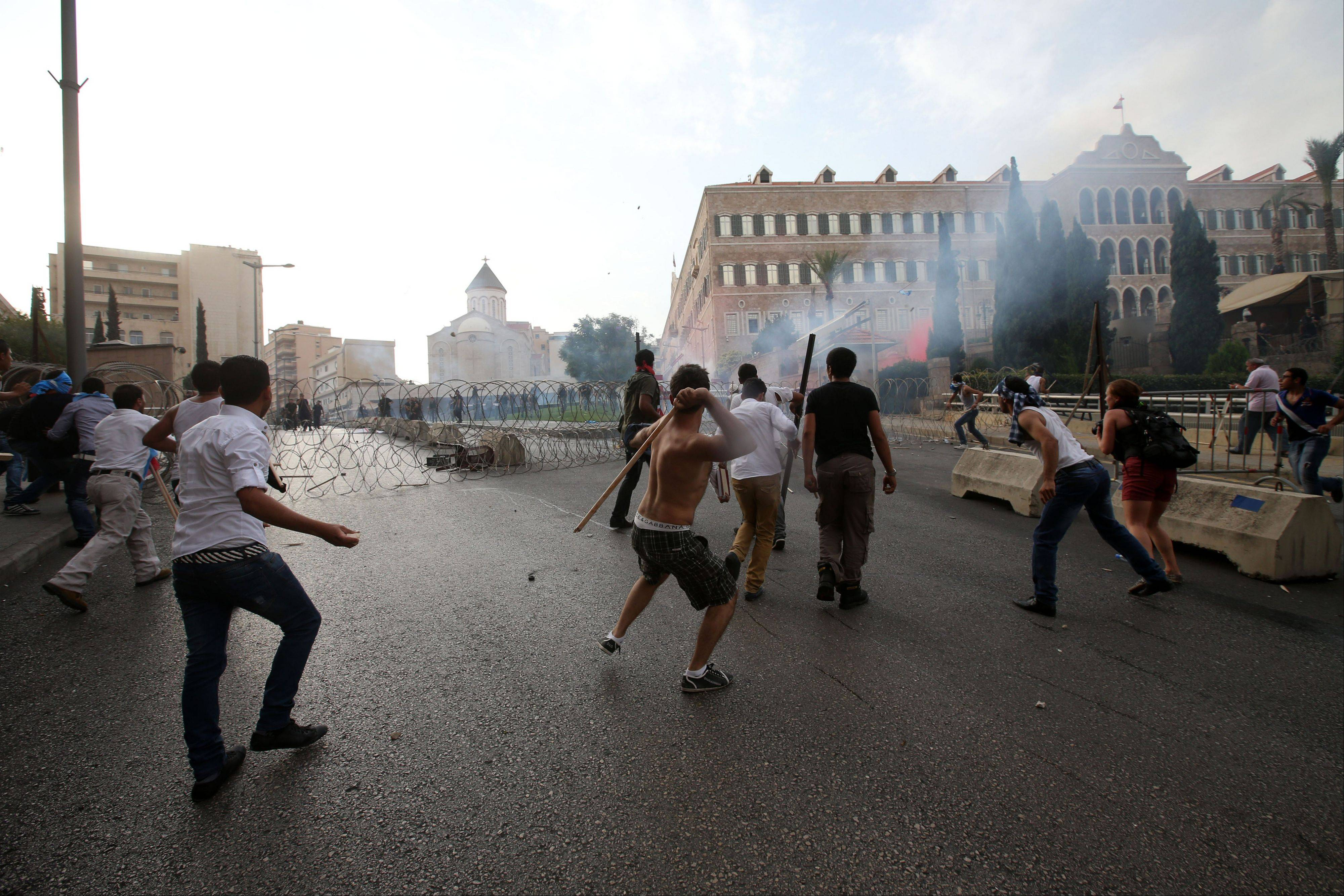 Lebanese protesters throw sticks and rocks Sunday during clashes with security forces after the funeral of Brig. Gen. Wissam al-Hassan who was assassinated on Friday by a car bomb in Beirut, Lebanon.