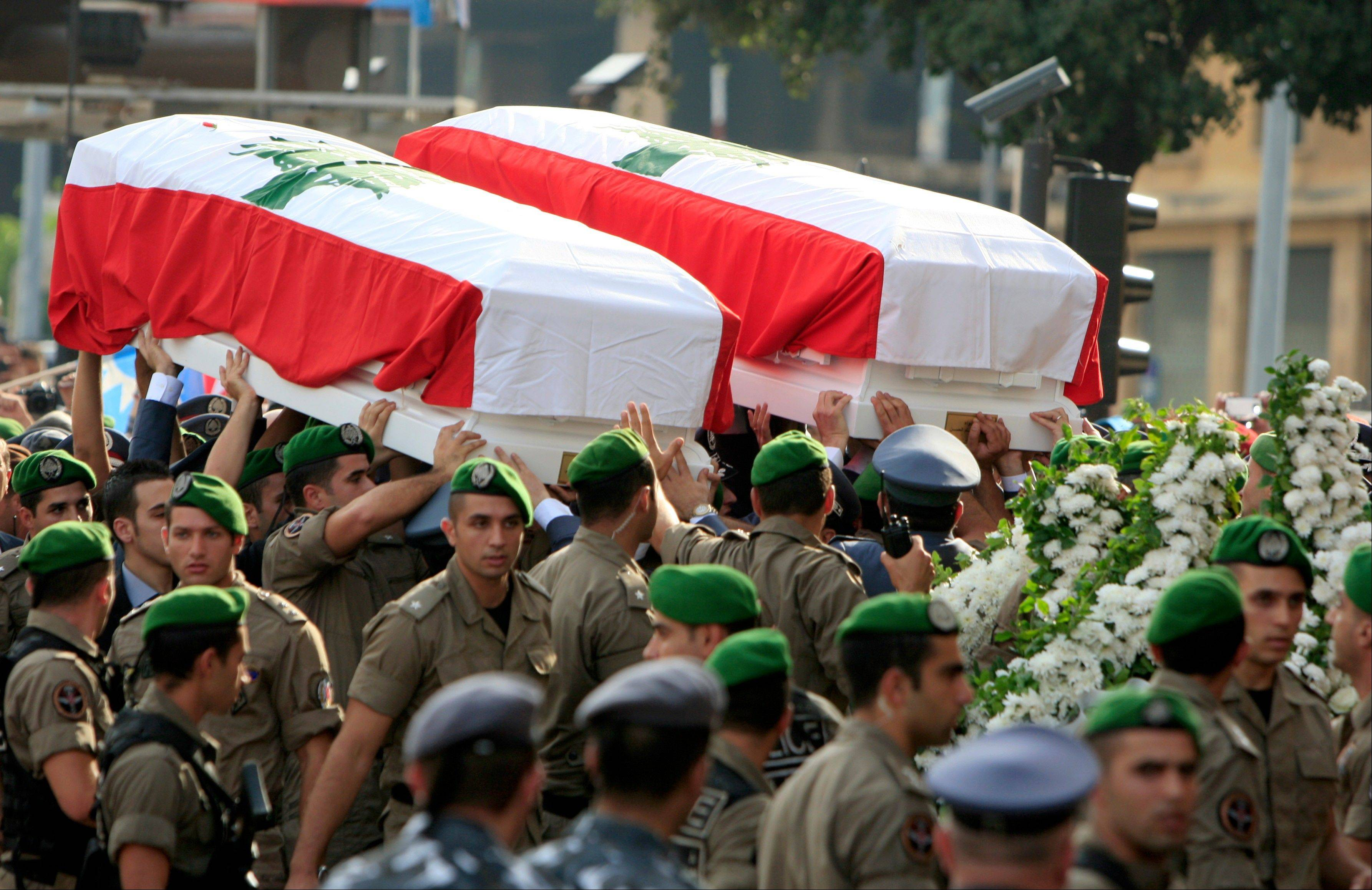 A Lebanese honor guard carries coffins wrapped with Lebanese flags of Brig. Gen. Wissam al-Hassan and his bodyguard, Ahmad Sahyouni, who were assassinated on Friday by a car bomb, during their funeral procession at Martyrs' Square in Beirut, Lebanon, Sunday. Thousands of Lebanese waving the national flag packed a central square in downtown Beirut Sunday for the funeral of a top intelligence official assassinated in a car bombing that many blame on the regime in neighboring Syria.