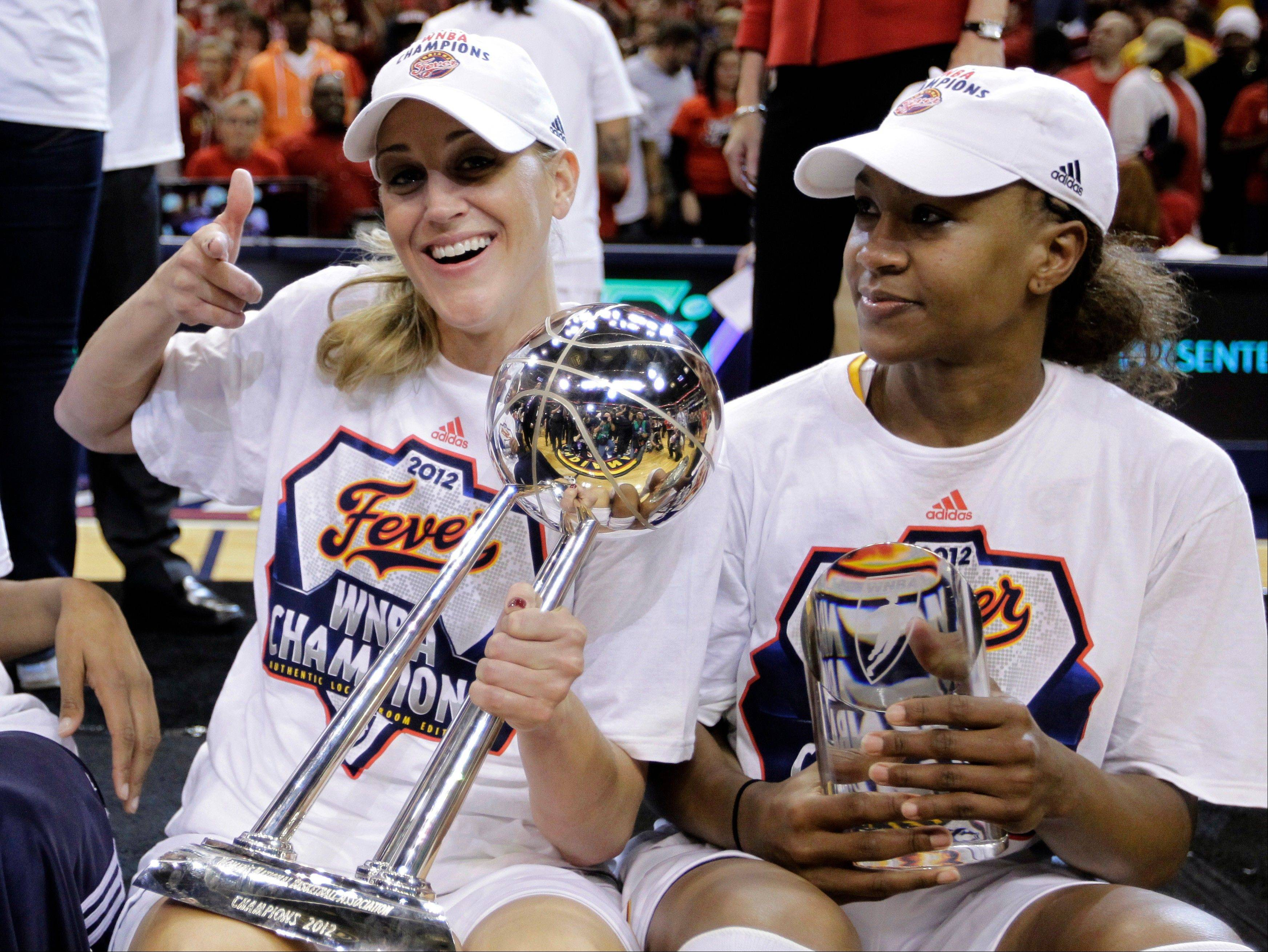 Indiana Fever guard Katie Douglas, left, and forward Tamika Catchings, the series MVP, pose with the trophies after winning the WNBA basketball Finals against the Minnesota Lynx in Indianapolis, Sunday, Oct. 21, 2012. The Fever won 87-78 to clinch their first WNBA championship.