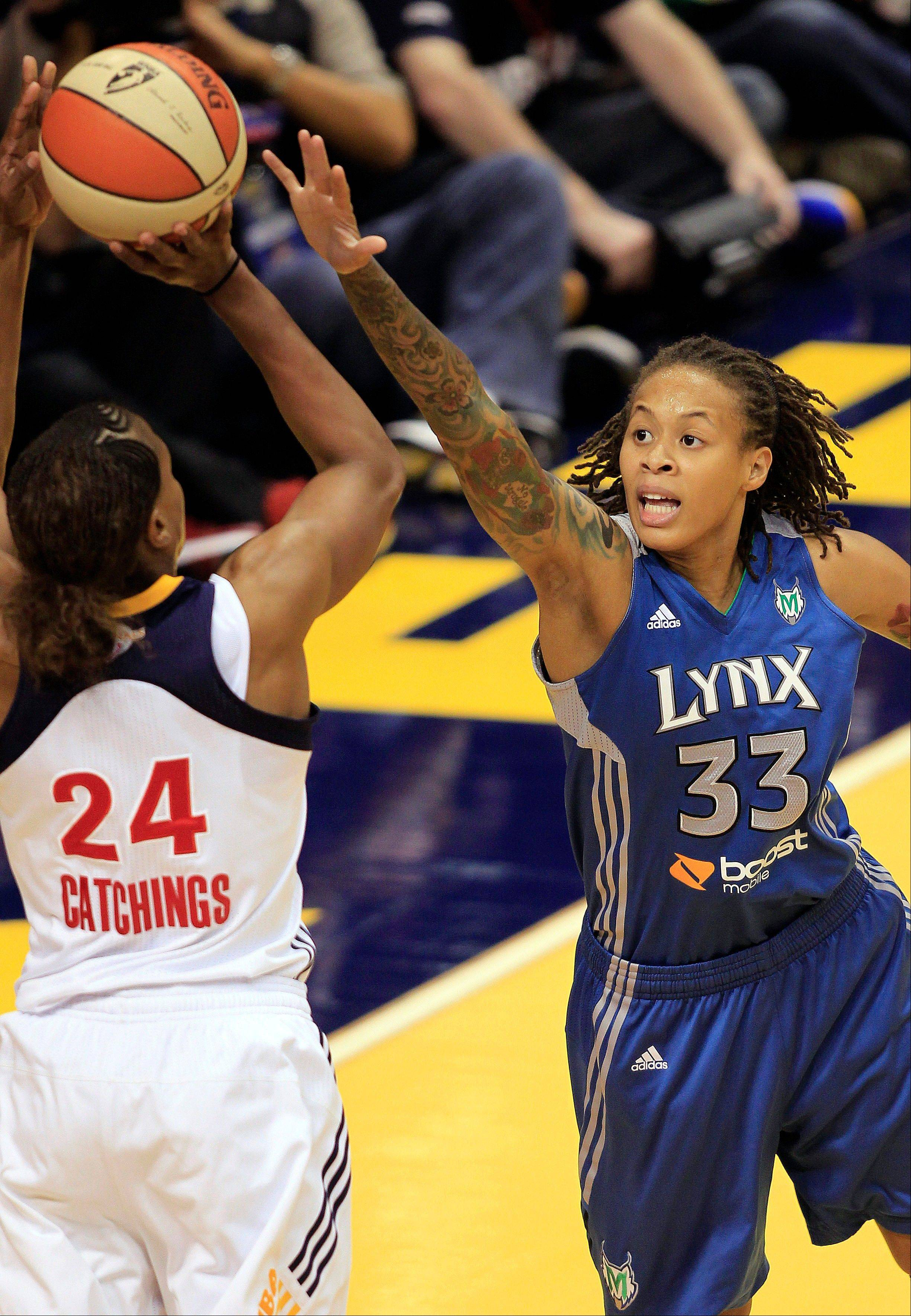 Minnesota Lynx guard Seimone Augustus, right, defends a shot by Indiana Fever forward Tamika Catchings in the first half of Game 4 of the WNBA basketball Finals Sunday, Oct. 21, 2012, in Indianapolis.
