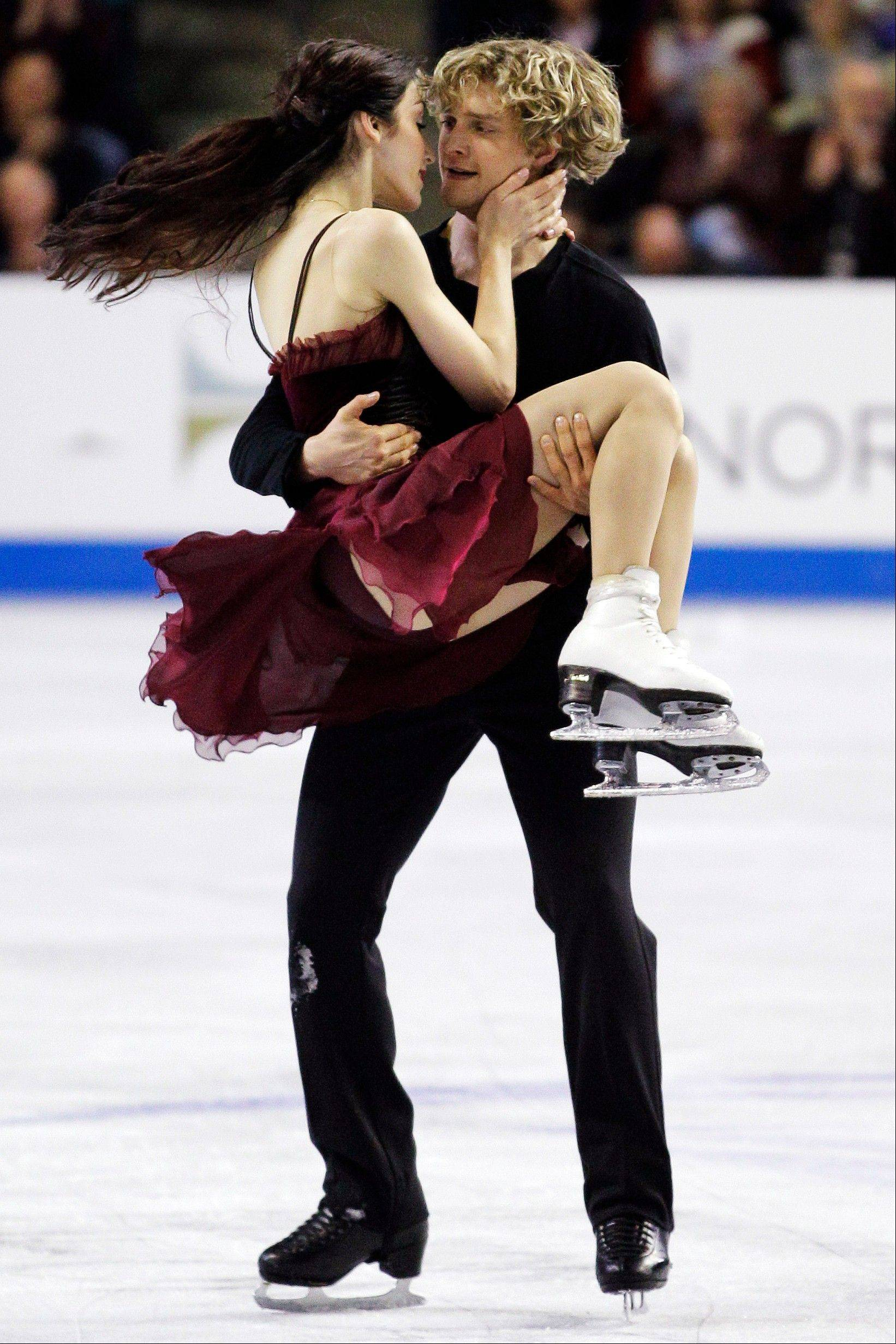 Charlie White picks up Meryl Davis after their first-place finish in the ice dancing event at Skate America.