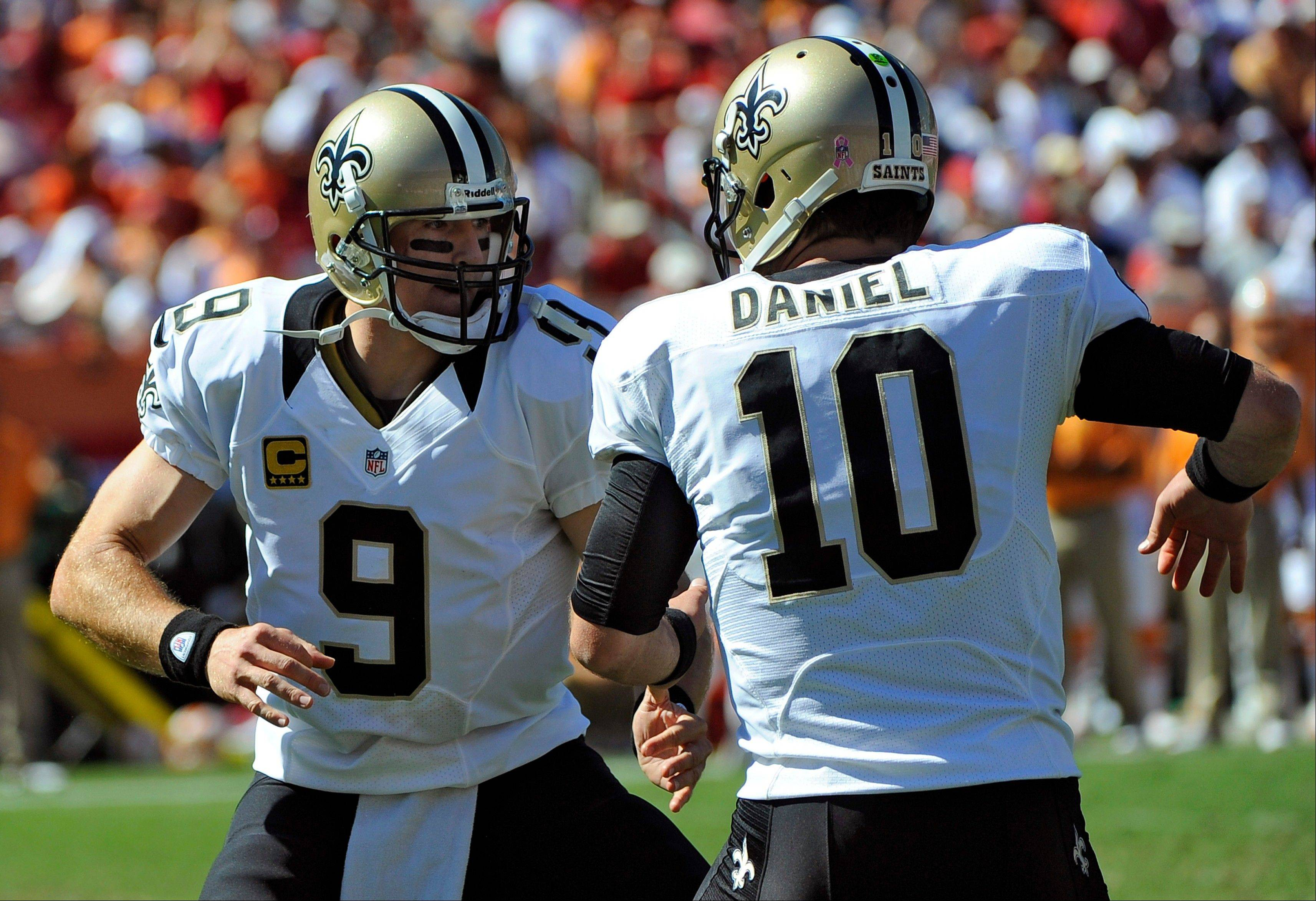 Saints quarterback Drew Brees celebrates with backup quarterback Chase Daniel after throwing a touchdown pass to tight end David Thomas against the Buccaneers on Sunday in Tampa, Fla.