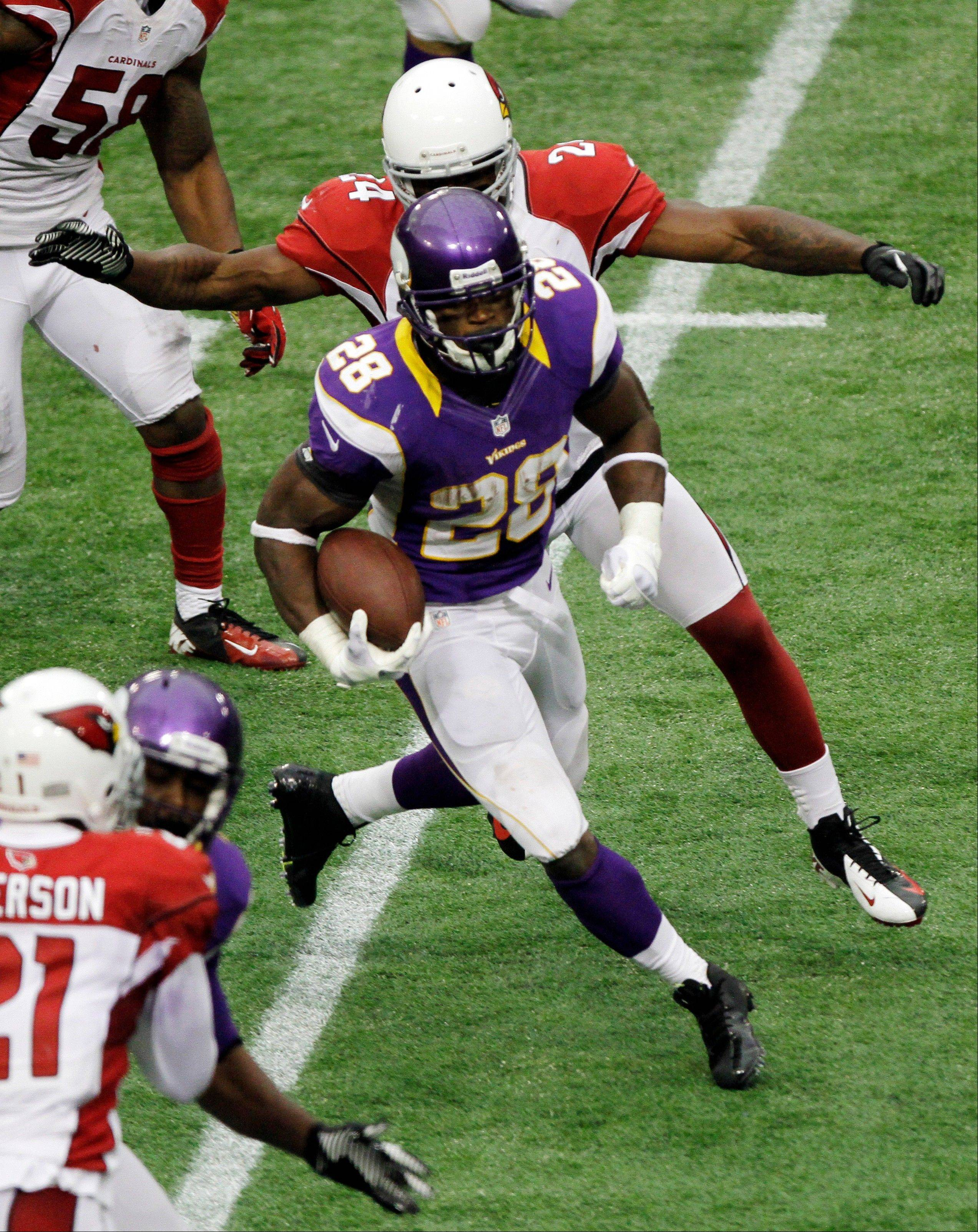 Minnesota Vikings running back Adrian Peterson rushes against Arizona Cardinals strong safety Adrian Wilson in the second half of Sunday's game in Minneapolis.