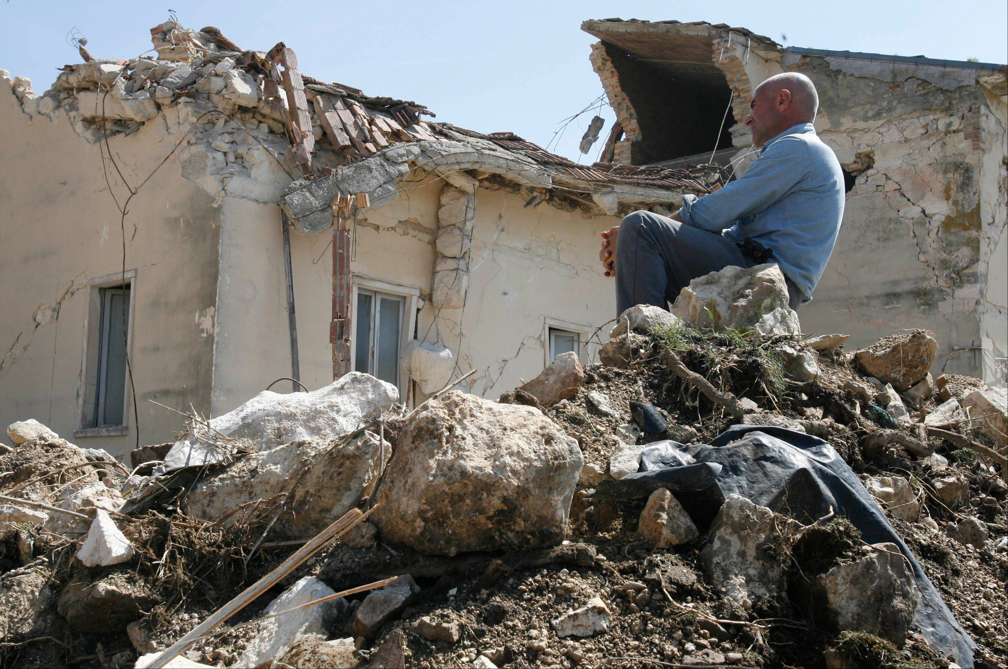 A man sits on rubbles in the village of Onna on April 7, a day after a powerful earthquake struck the Abruzzo region in central Italy.