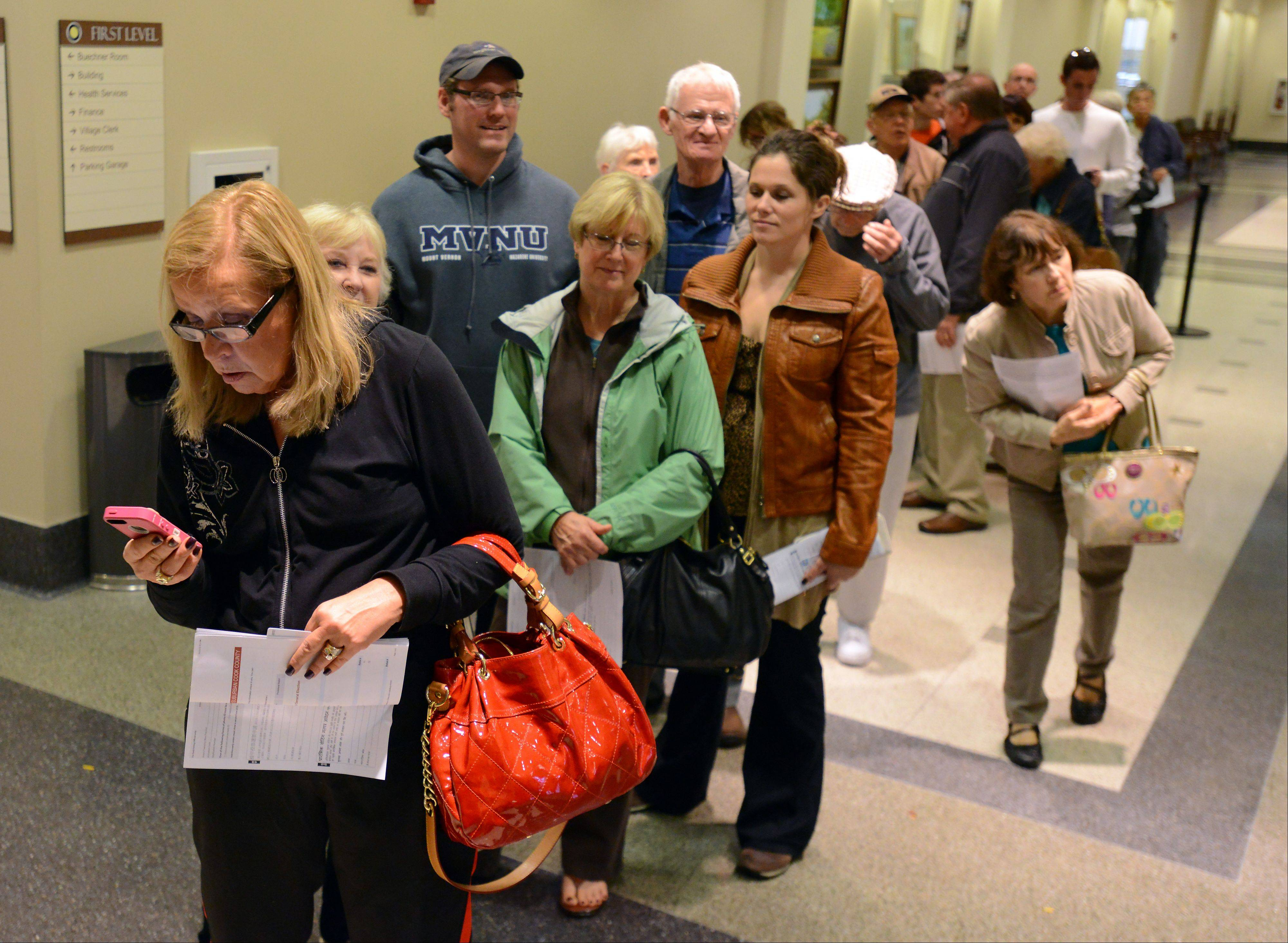 Sandie Campo of Arlington Heights holds her voter information as she stands in a long line of early voters at the Arlington Heights village hall on Monday. Village hall was the second most popular early voting location Monday in suburban Cook County.