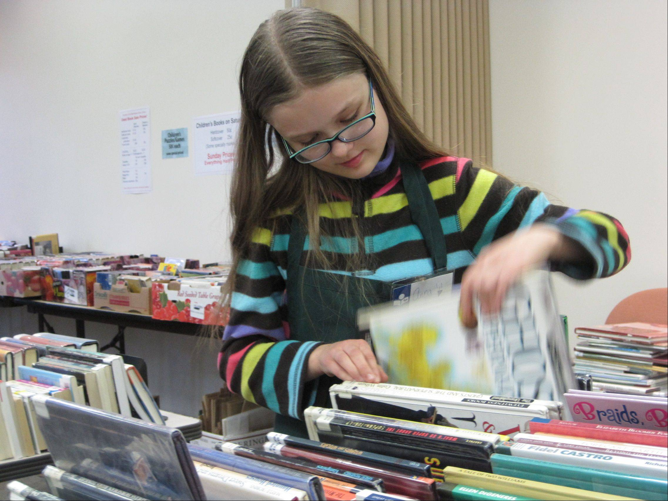 Anna Walker, 13, looks through children�s books Saturday at the Friends of the Barrington Area Library book sale.