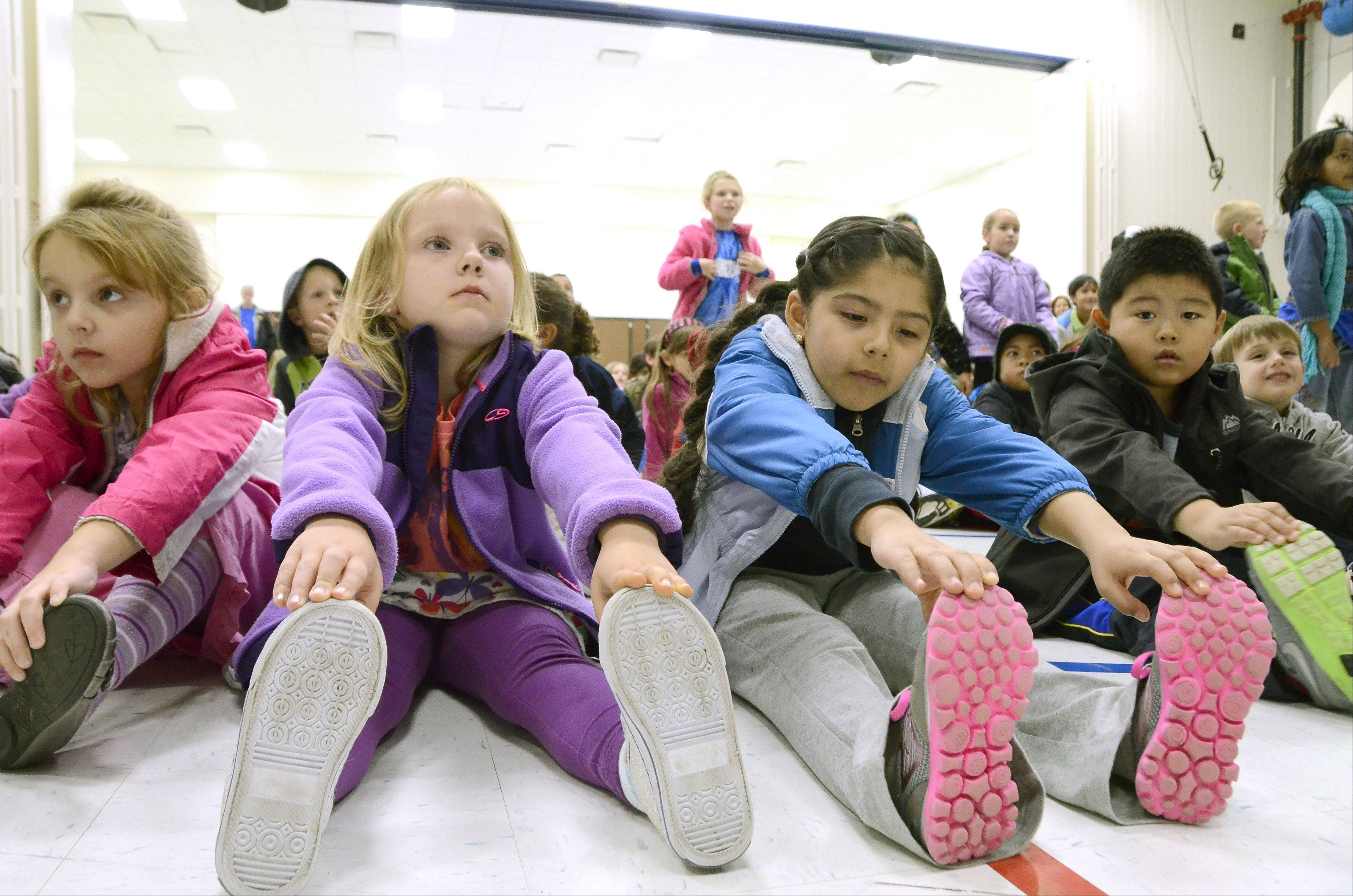 Students from Cumberland Elementary School in Des Plaines warm-up with stretches before walking Friday afternoon to raise money for new playground equipment.