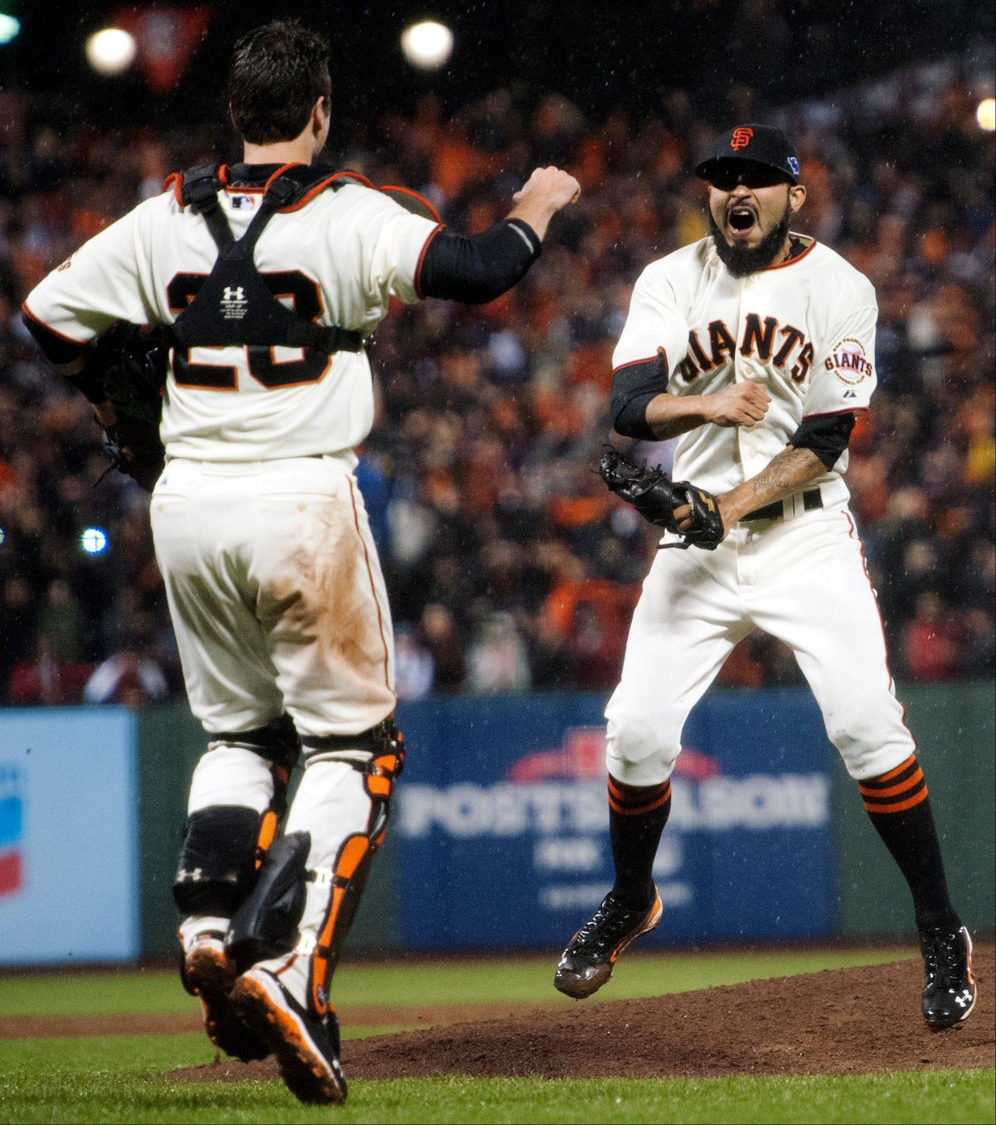 Giants catcher Buster Posey and relief pitcher Sergio Romo celebrate the final out of Game 7 of the National League championship series against the St. Louis Cardinals on Monday in San Francisco.