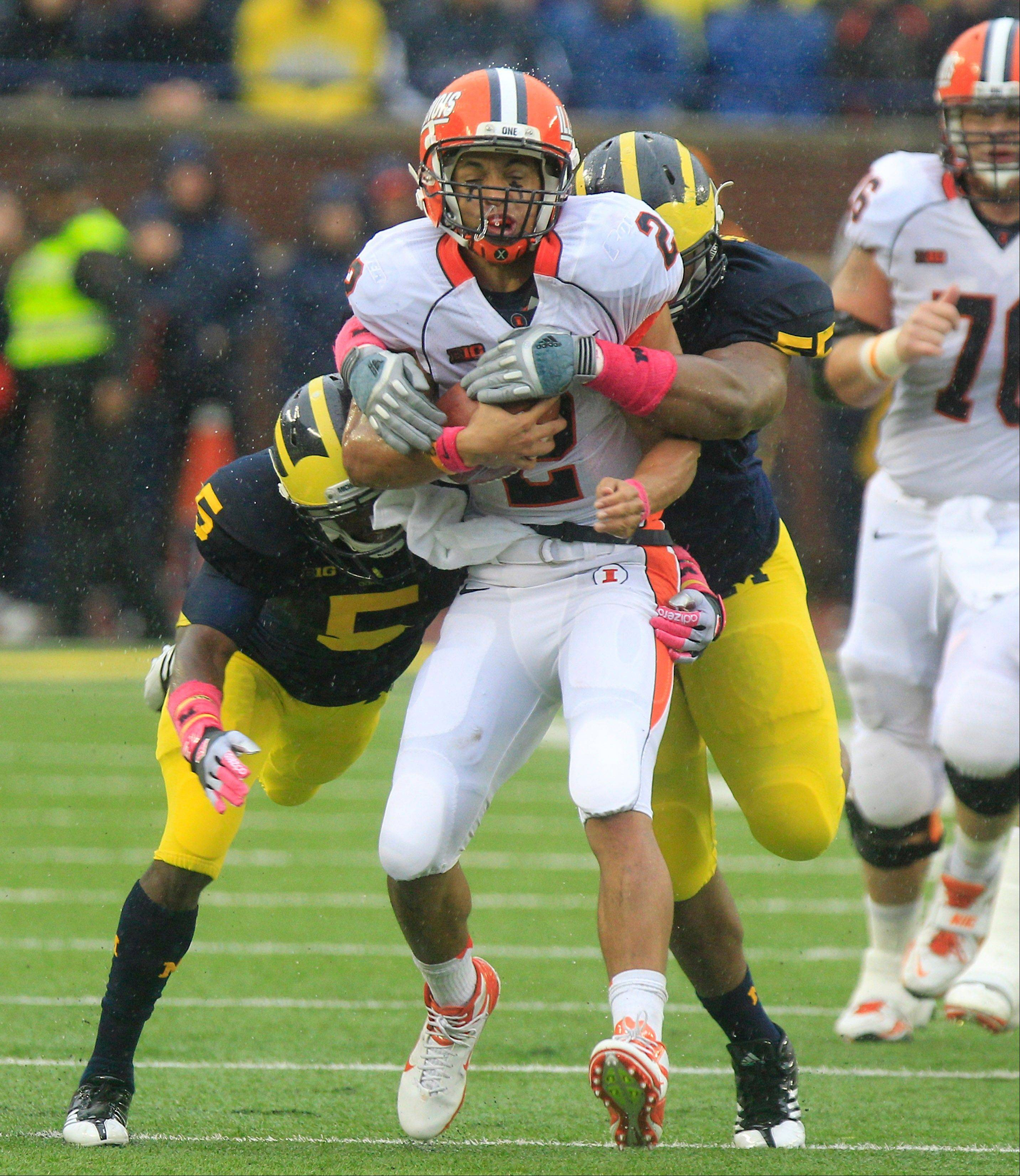 Michigan cornerback Courtney Avery (5) and defensive tackle Jibreel Black wrap up Illinois quarterback Nathan Scheelhaase in the second quarter of the Wolverines� 45-0 pummeling of the Illini on Oct. 13. Scheelhaase was injured on the play.