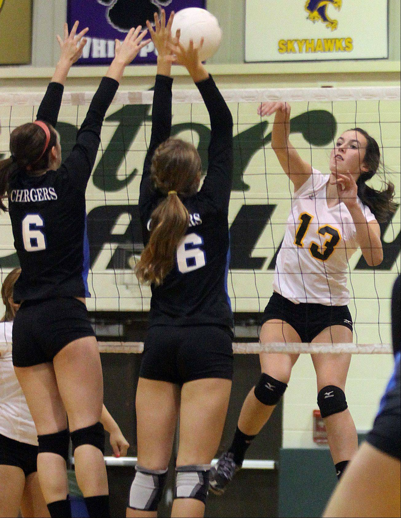 Jacobs� Katie Mahoney, right, hits the ball as Dundee-Crown�s Gina Pagano and Kathryn Novy block during a regional game at Crystal Lake South High School on Monday night.