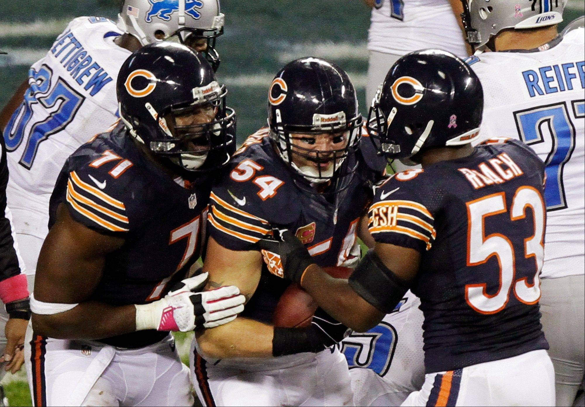 Chicago Bears linebacker Brian Urlacher (54) celebrates with Israel Idonije (71) and Nick Roach (53) after he recovered fumble against the Detroit Lions near the goal line in the second half of an NFL football game in Chicago, Monday, Oct. 22, 2012.