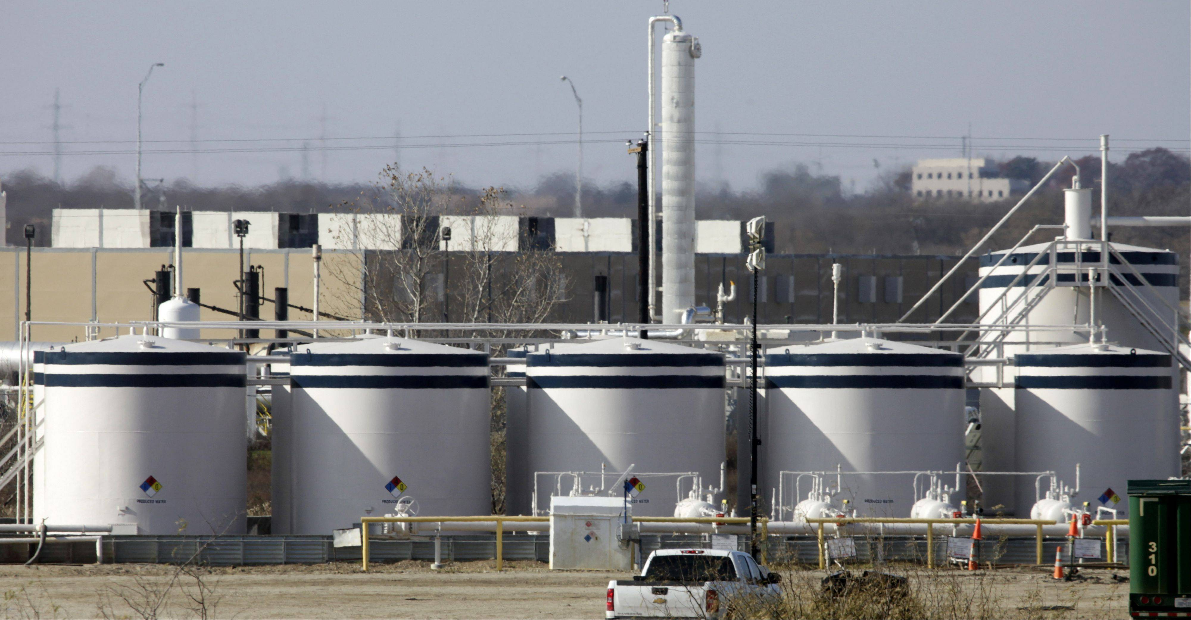 Natural gas holding tanks sit near a drilling sight in Grapevine, Texas. Natural gas prices are dropping.