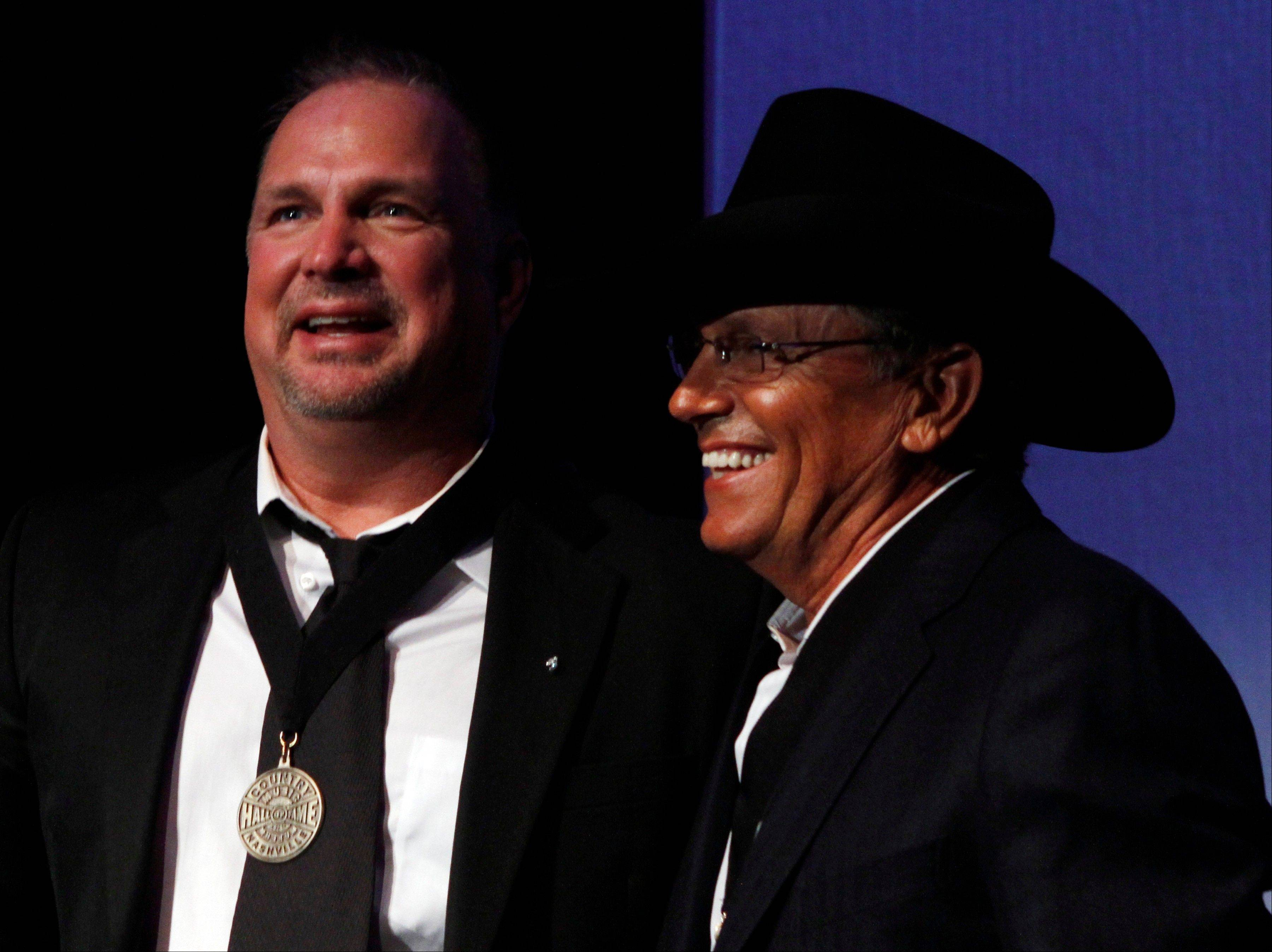 Garth Brooks, left, stands with George Strait after being inducted into the Country Music Hall of Fame on Sunday in Nashville, Tenn.