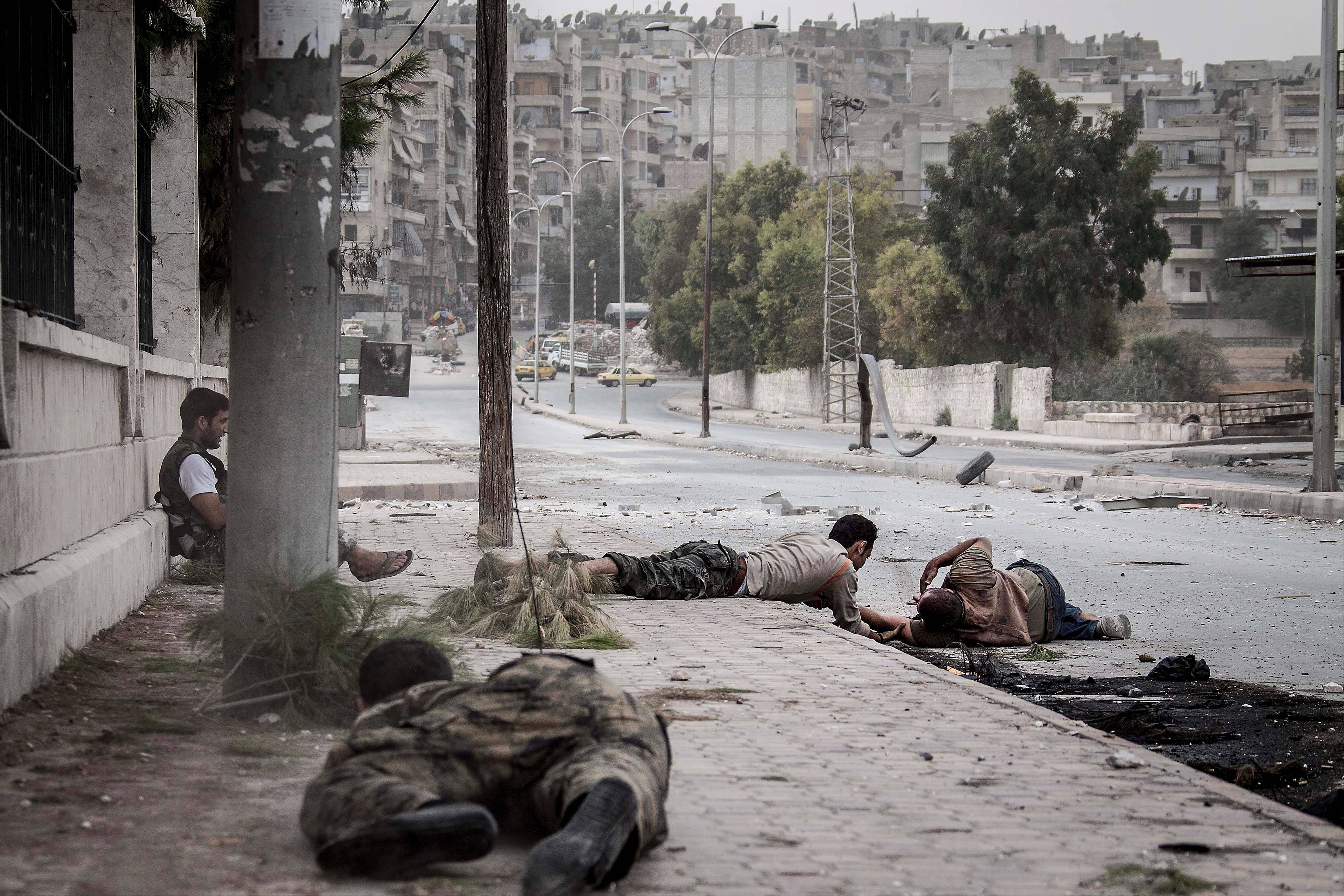 Free Syrian Army fighters crawl on the sidewalk Saturday as they attempt to rescue a Syrian civilian who was shot twice, in his stomach and his back, by a Syrian army sniper while he was walking on the front line in the Bustan al-Qasr neighborhood of Aleppo, Syria.