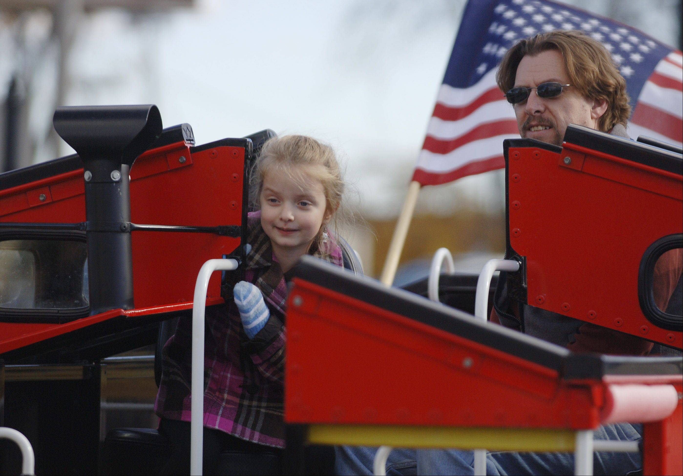 Josephine Tilford, 5 of Round Lake, climbs aboard the Canadian National�s Little Obie train with her dad, John Tilford, during the Mundelein Fall Harvest Celebration Friday. The fest was held to officially close the Mundelein Farmers Market for the season.