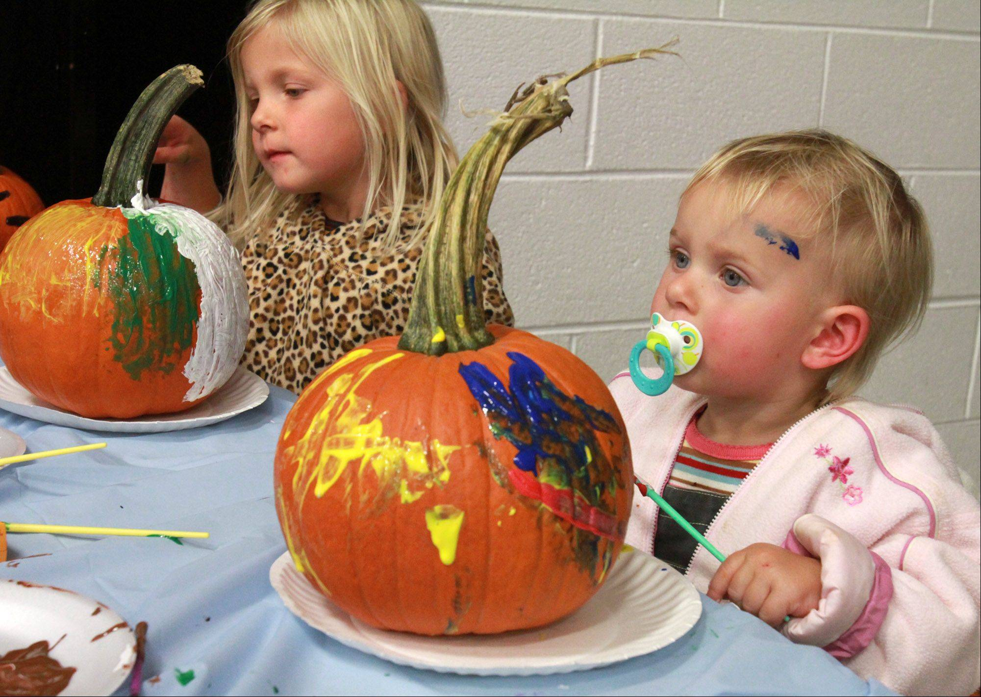 18-month-old Lucy Gross and her sister Oletta, 4, both of Barrington paint pumpkins at Hough Street School in Barrington on Saturday, October 13. The event was moved indoors from Memorial Park due to rain.