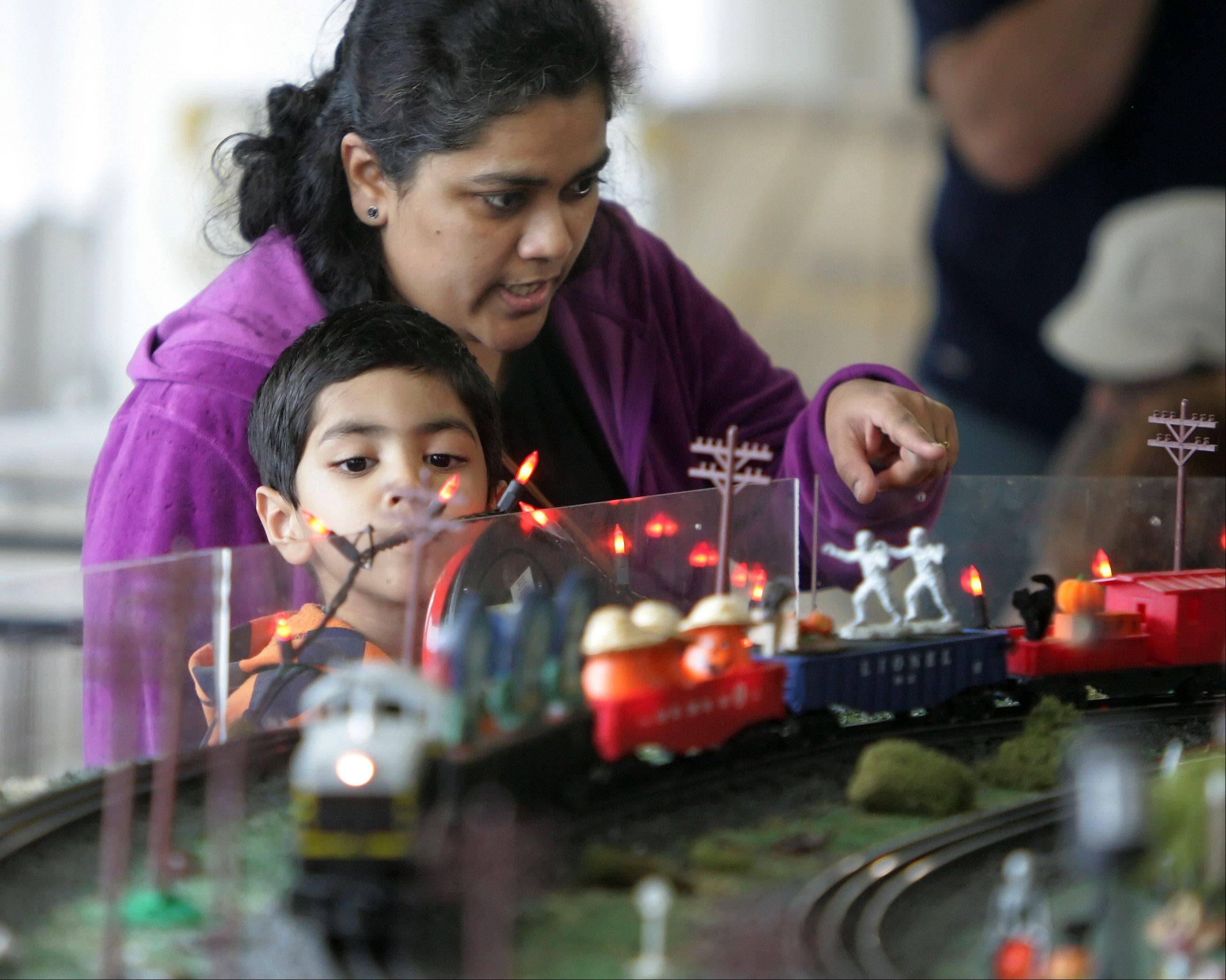 Deeoti Mishrikotkar, of Mundelein, brings her son, Neil, 4, to see the Halloween model train display by the North Central O Gaugers Model Railroad Club Sunday at the Fremont Public Library in Mundelein. The display featured giant spiders, space aliens, ghouls, mummies and witches, and lots of trains.
