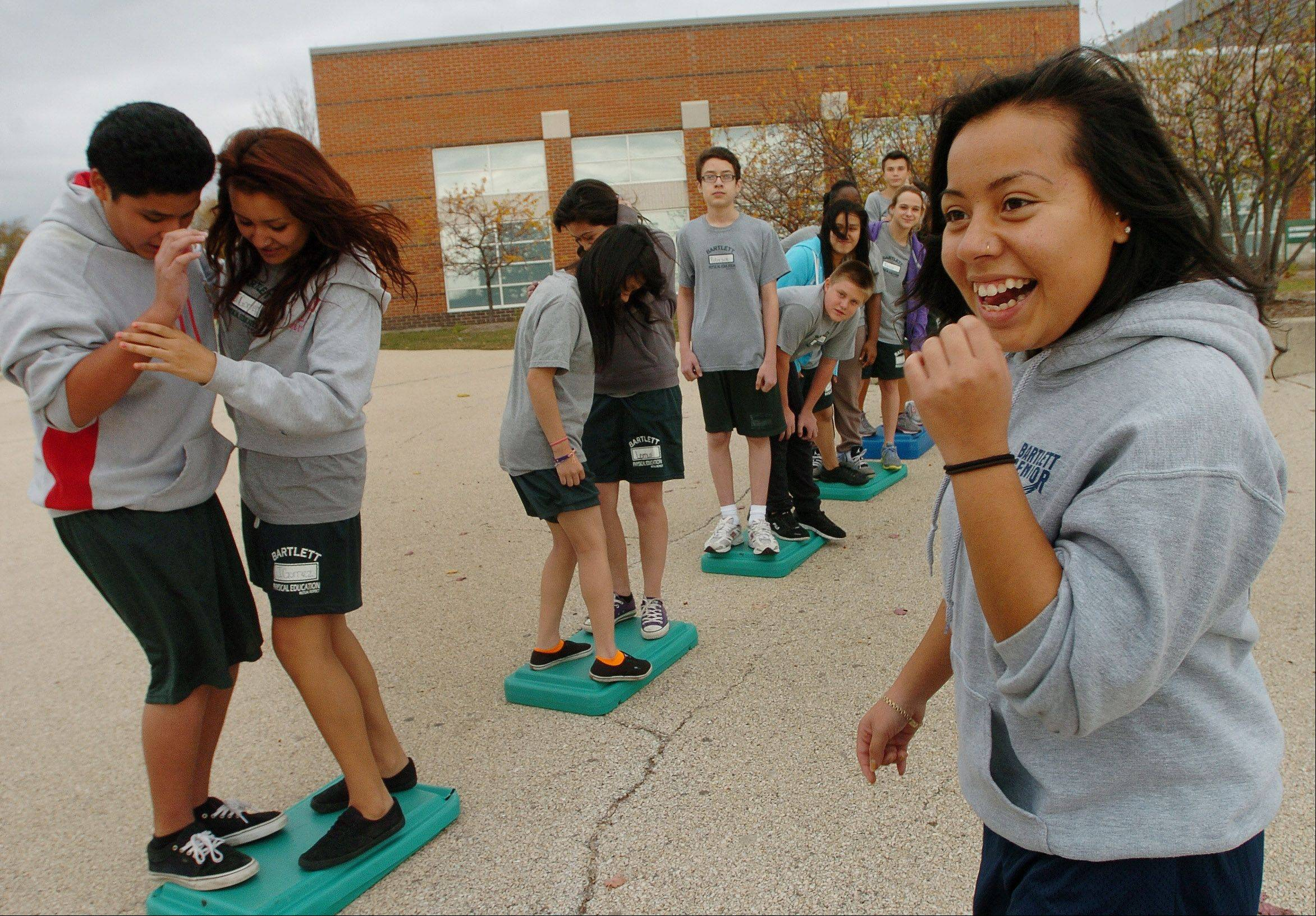 Selena Cuevas, right, guides freshmen through a team building exercise during a Bartlett High School senior leaders program.