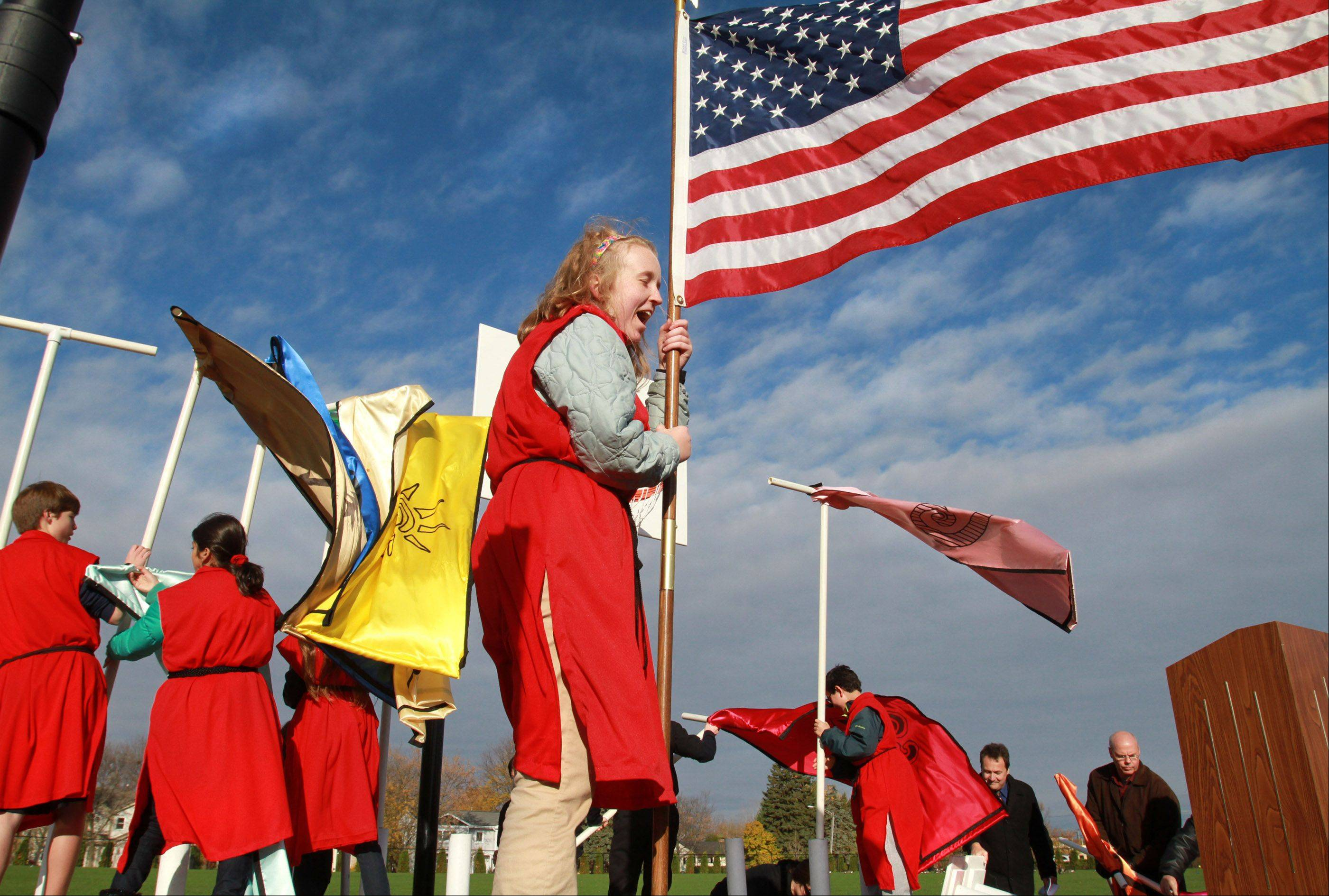 Hannah O'Brien, 14, eight-grader at Quest Academy, raises to and grips the American flag as a wind gust toppled banners and flags onstage at the school's ribbon-cutting and preview ceremony for its 3.68-acre outdoor West Campus in Palatine on Thursday, October 18. All Quest students, faculty, administration, about 200 parents, and Palatine Mayor Mr. Jim Schwantz attended.