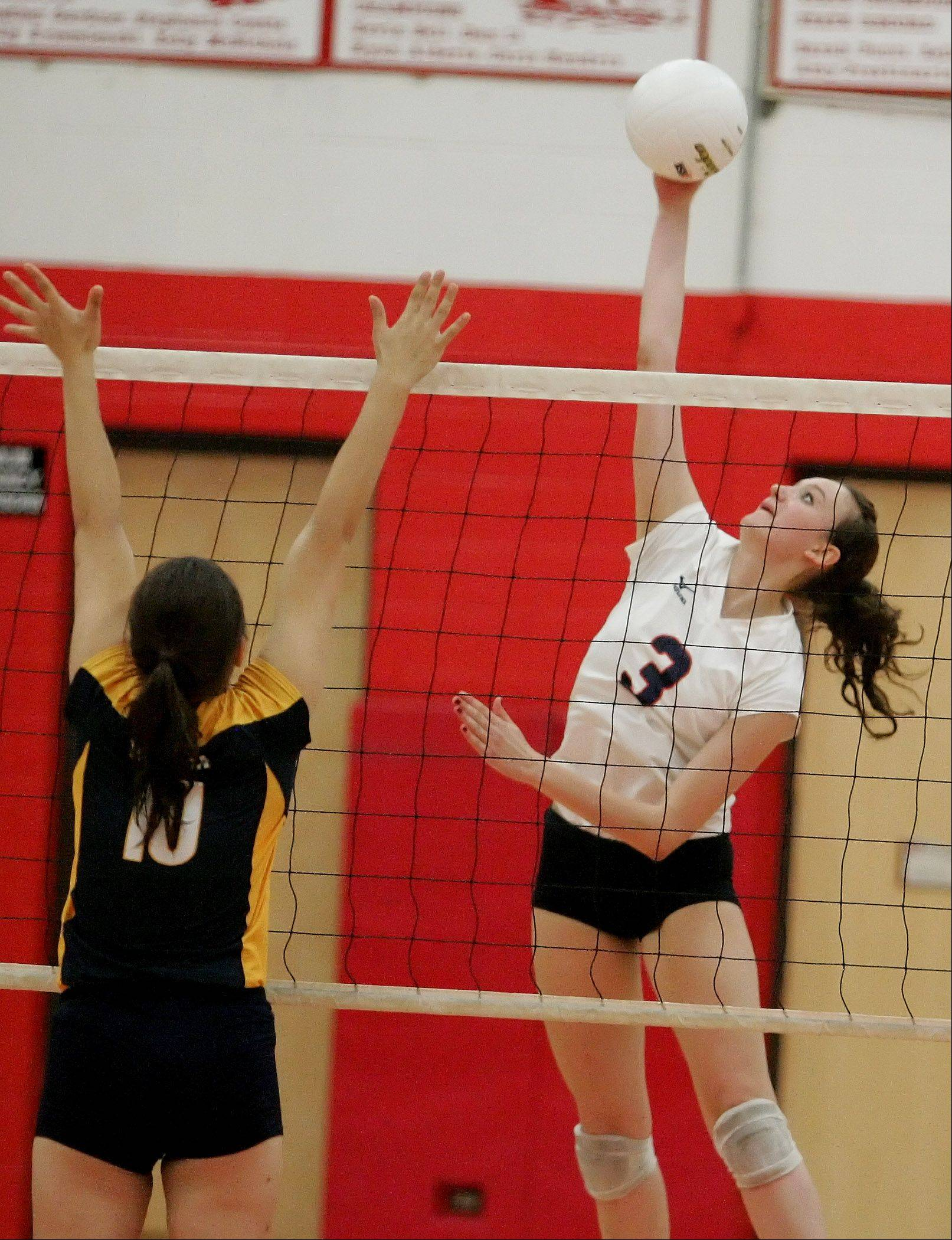 Angela Jurek of Naperville Northspikes the ball as Stephanie Vas, left, of Neuqua Valley defends in Class 4A girls volleyball regional semifinals at Naperville Central on Monday.