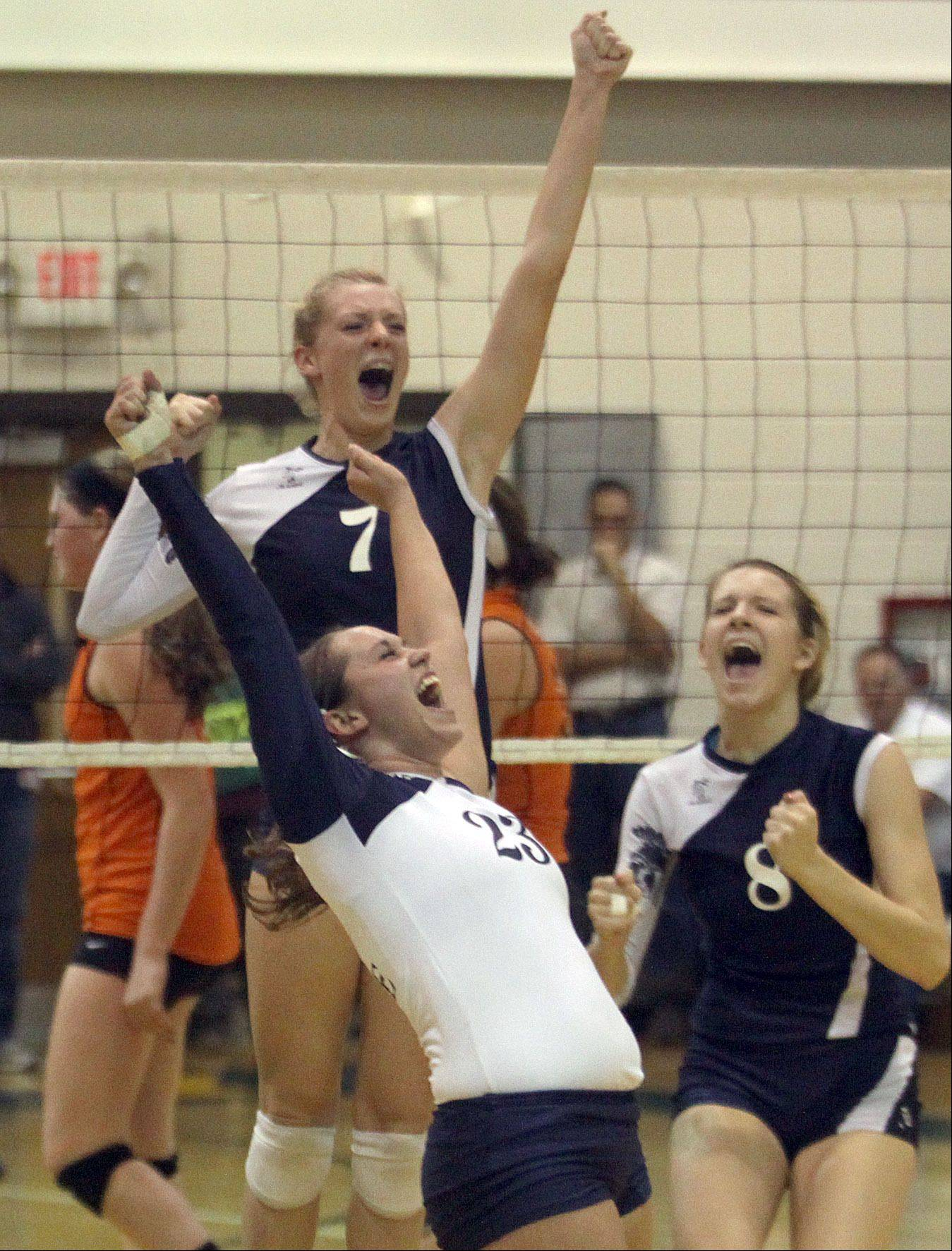 Cary-Grove players Morgan Lee, upper left, Micah Duzey, lower left, and Abby Schebel, right celebrate a regional game victory over Crystal Lake Central at Crystal Lake South High School on Monday night.