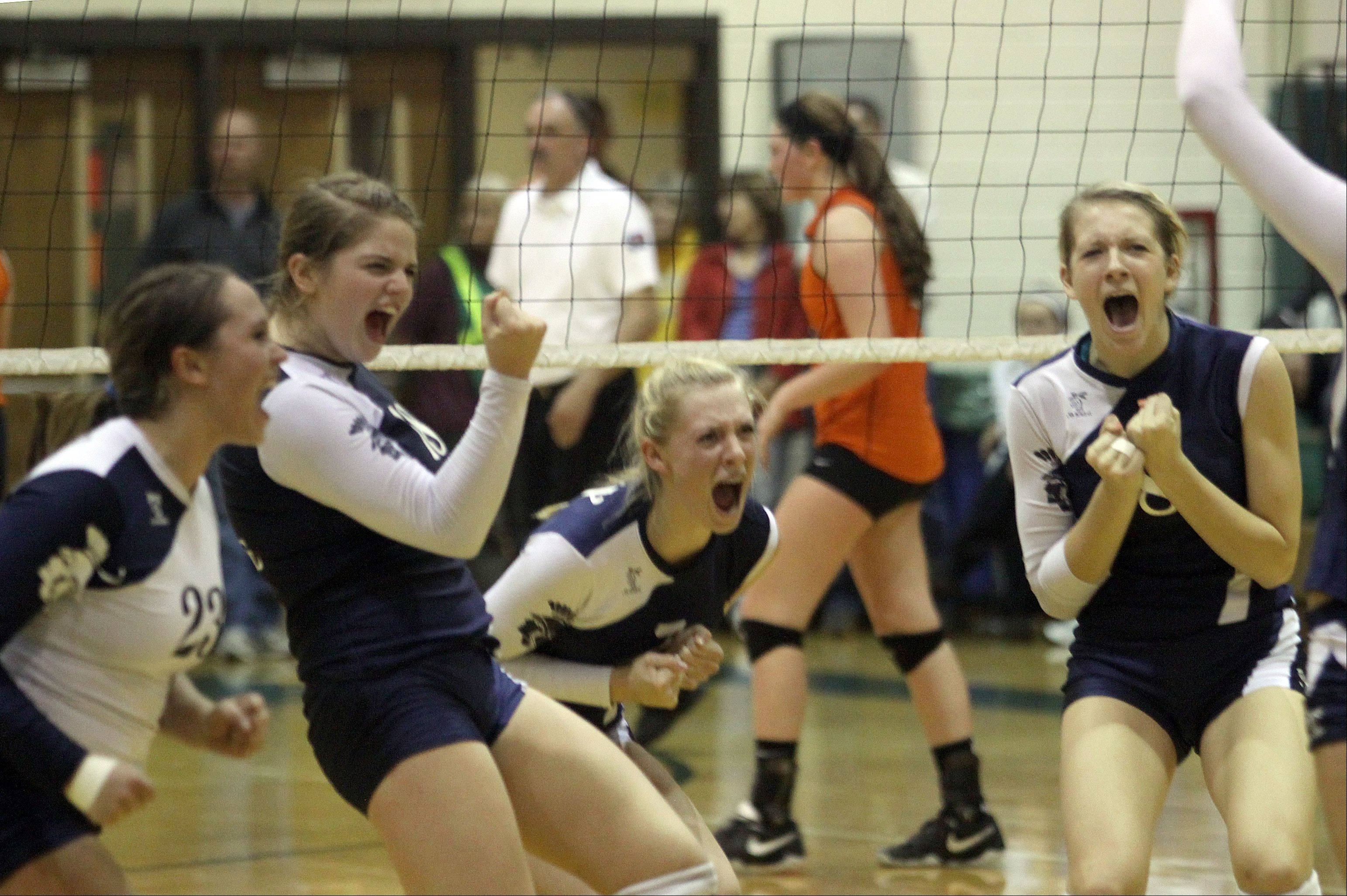 Cary-Grove players, from left, Micah Duzey, Ally Vasquez, Morgan Lee, and Abby Schebel celebrate a regional game victory over Crystal Lake Central at Crystal Lake South High School on Monday night.