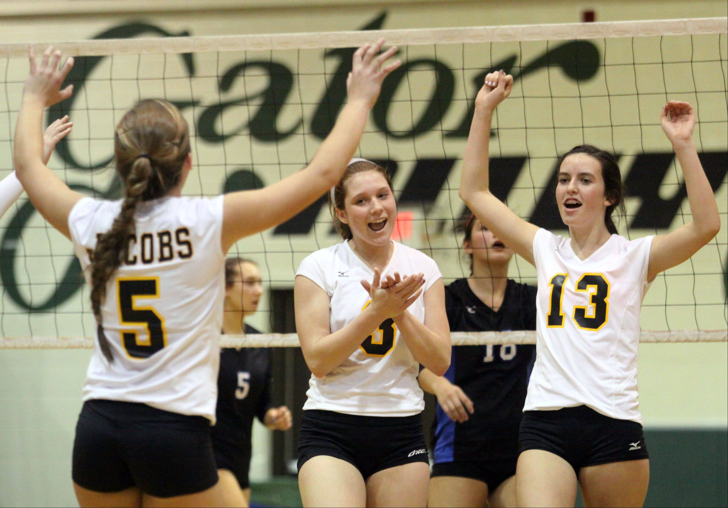 Jacobs' players, from left, Maris Smith, Alyssa Ehrhardt, and Katie Mahoney celebrate a victory over Dundee-Crown in a regional game at Crystal Lake South High School on Monday night.