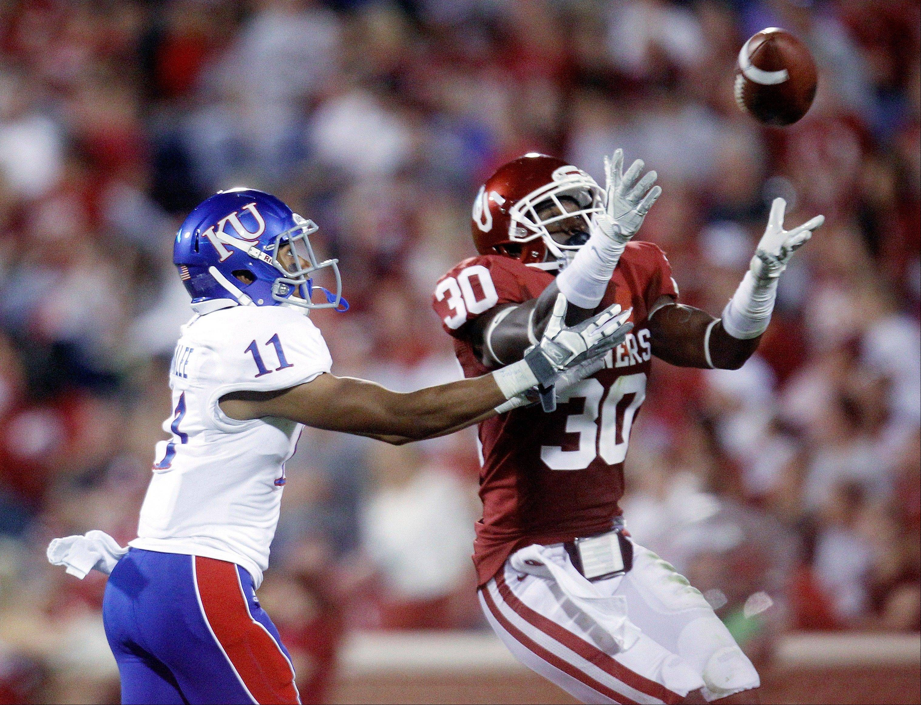 Oklahoma defensive back Javon Harris (30) intercepts a pass intended for Kansas wide receiver Tre' Parmalee (11) during the fourth quarter of an NCAA college football game in Norman, Okla., Saturday, Oct. 20, 2012. Oklahoma won 52-7.