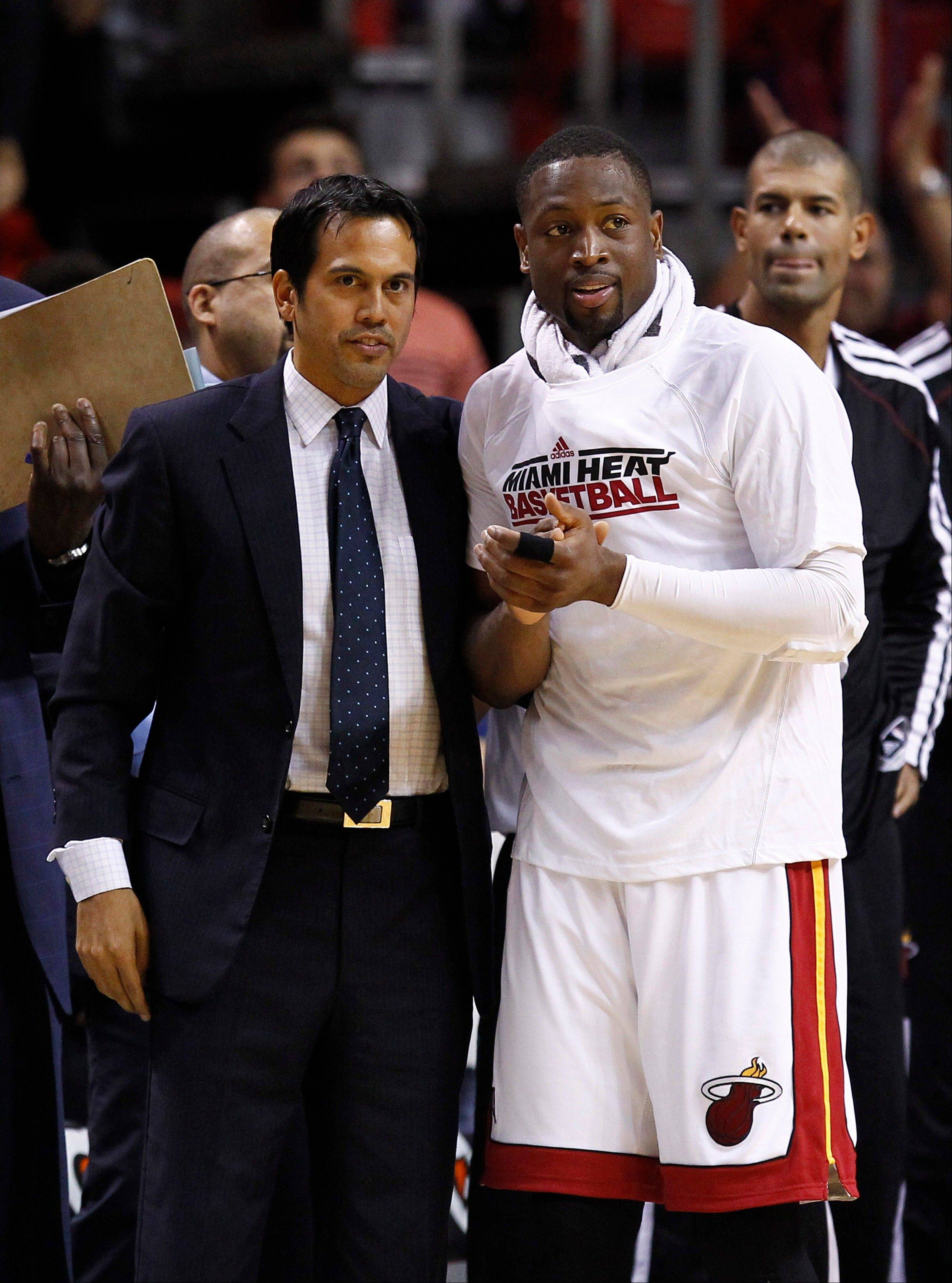According to a survey of league GMs, Miami Heat coach Erik Spoelstra, left, and Dwyane Wade will be heading back to the NBA Finals this season.