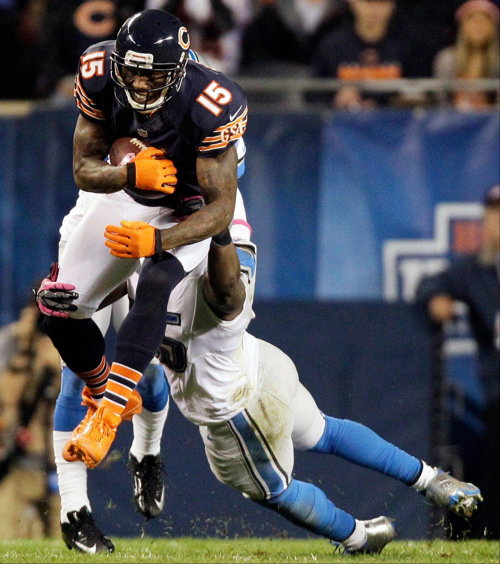 Chicago Bears wide receiver Brandon Marshall (15) is tackled by Detroit Lions linebacker Stephen Tulloch in the first half of an NFL football game in Chicago, Monday, Oct. 22, 2012.