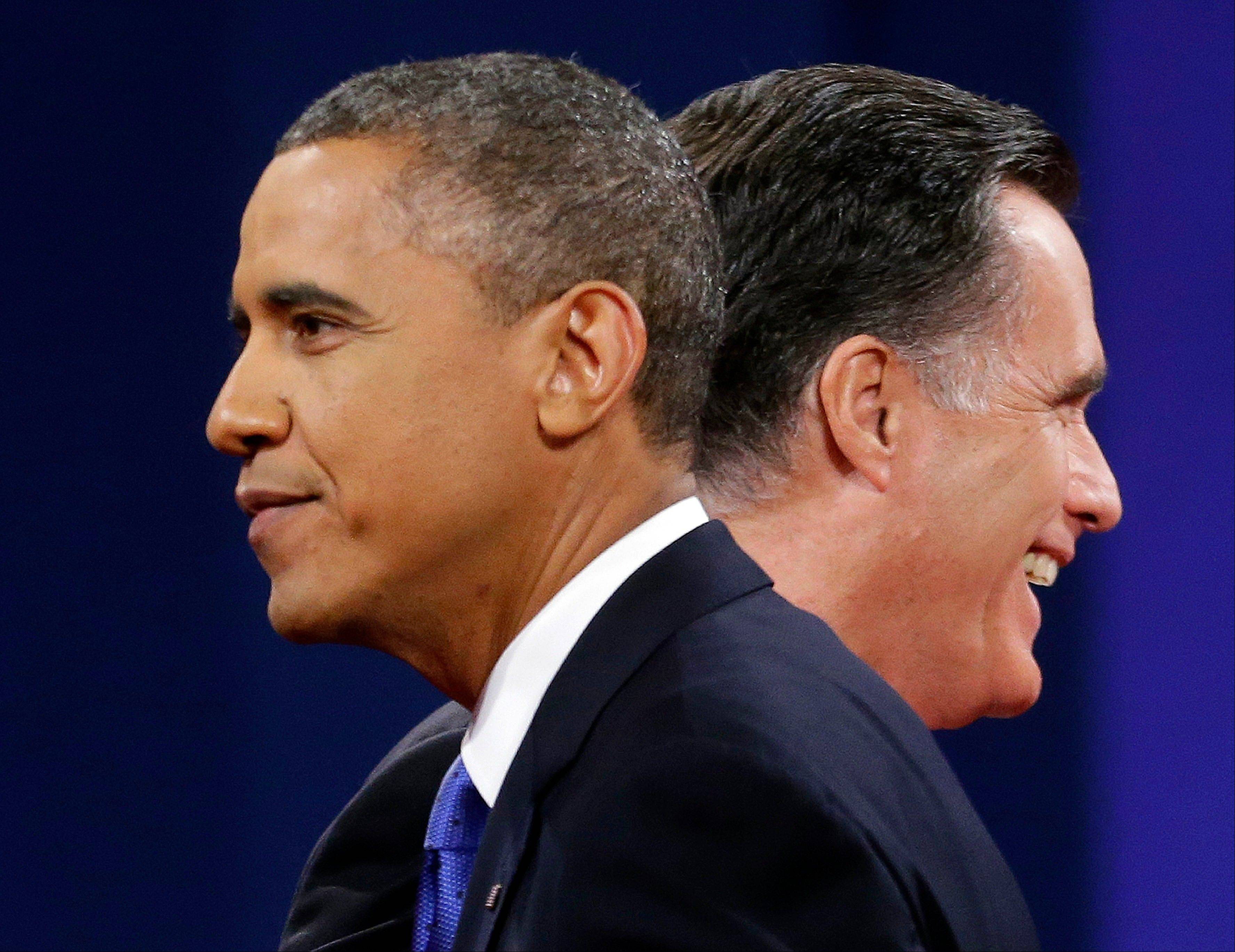 Republican presidential candidate, former Massachusetts Gov. Mitt Romney and President Barack Obama walks past each other onstage at the end of the last debate at Lynn University, Monday, Oct. 22, 2012, in Boca Raton, Fla.
