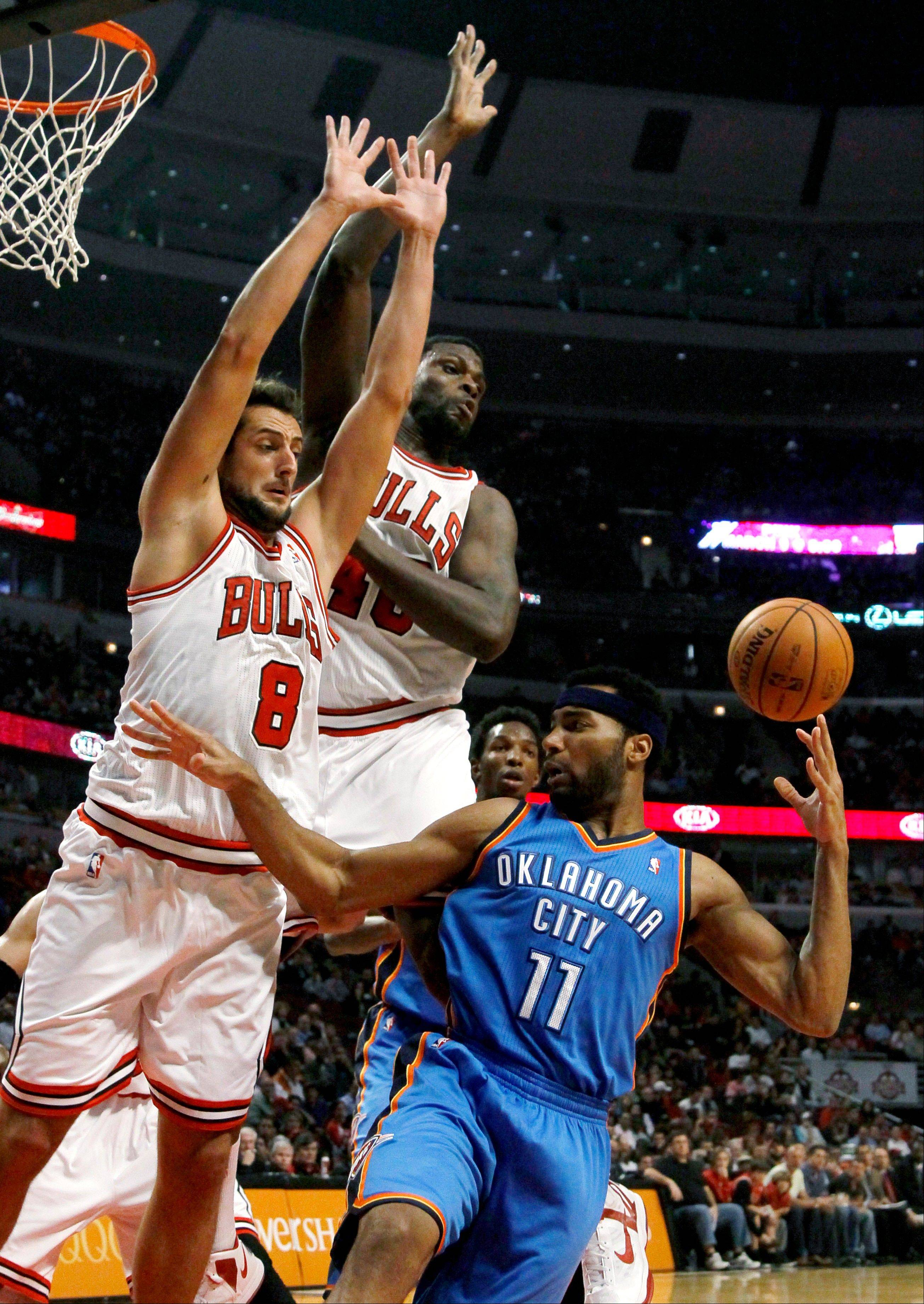 Oklahoma City Thunder small forward Lazar Hayward (11) passes behind his head as Chicago Bulls shooting guard Marco Belinelli (8) and center Nazr Mohammed defend during the first half of an NBA preseason basketball game, Tuesday, Oct. 23, 2012, in Chicago. (AP Photo/Charlie Arbogast)