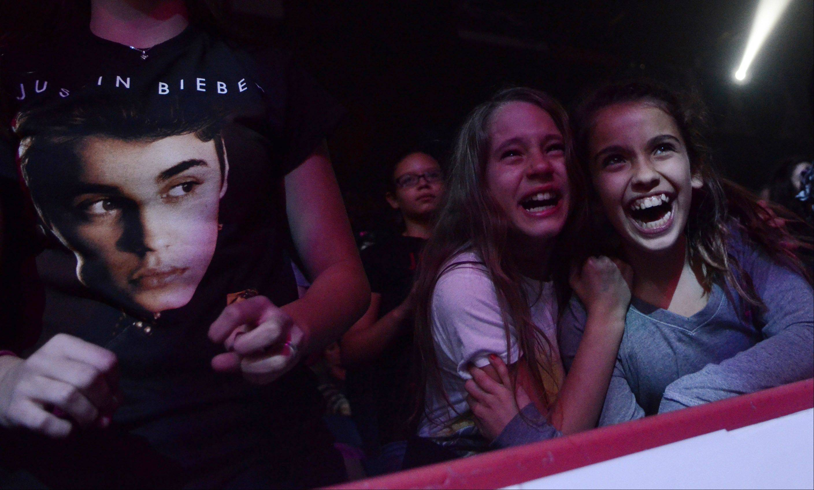 Sheridan Young, 11, left, and her friend Madison White, 10, both of Lake Bluff, cheer as they watch Justin Bieber perform during his Believe tour at the Allstate Arena in Rosemont on Tuesday, October 23, 2012.