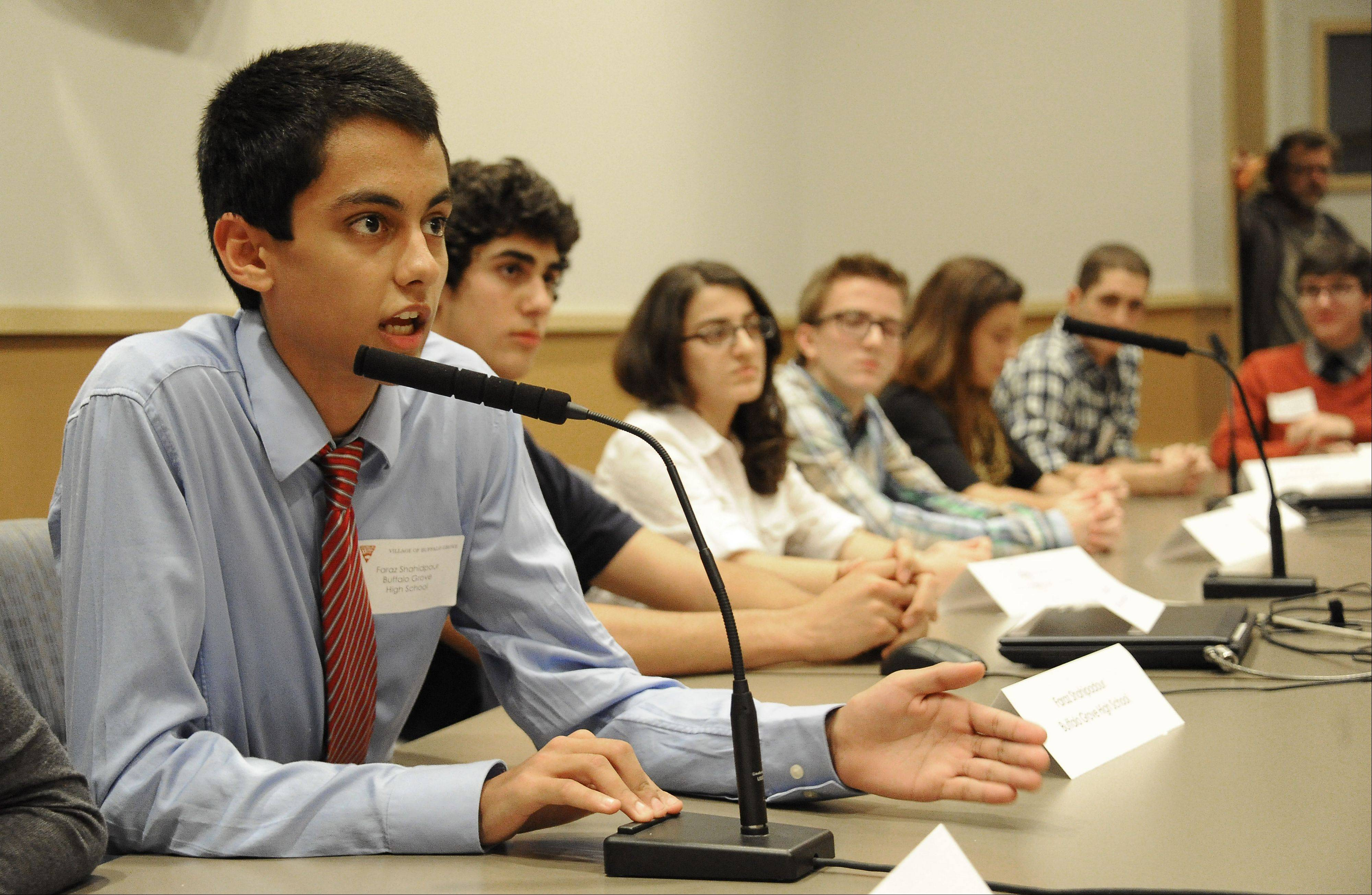 "Faraz Shahidpour, 17, of Buffalo Grove High School presents results and answers questions from village trustees at the village hall in Buffalo Grove on Monday about research on the issue ""Should the village legislate an age restriction of tanning beds?"""