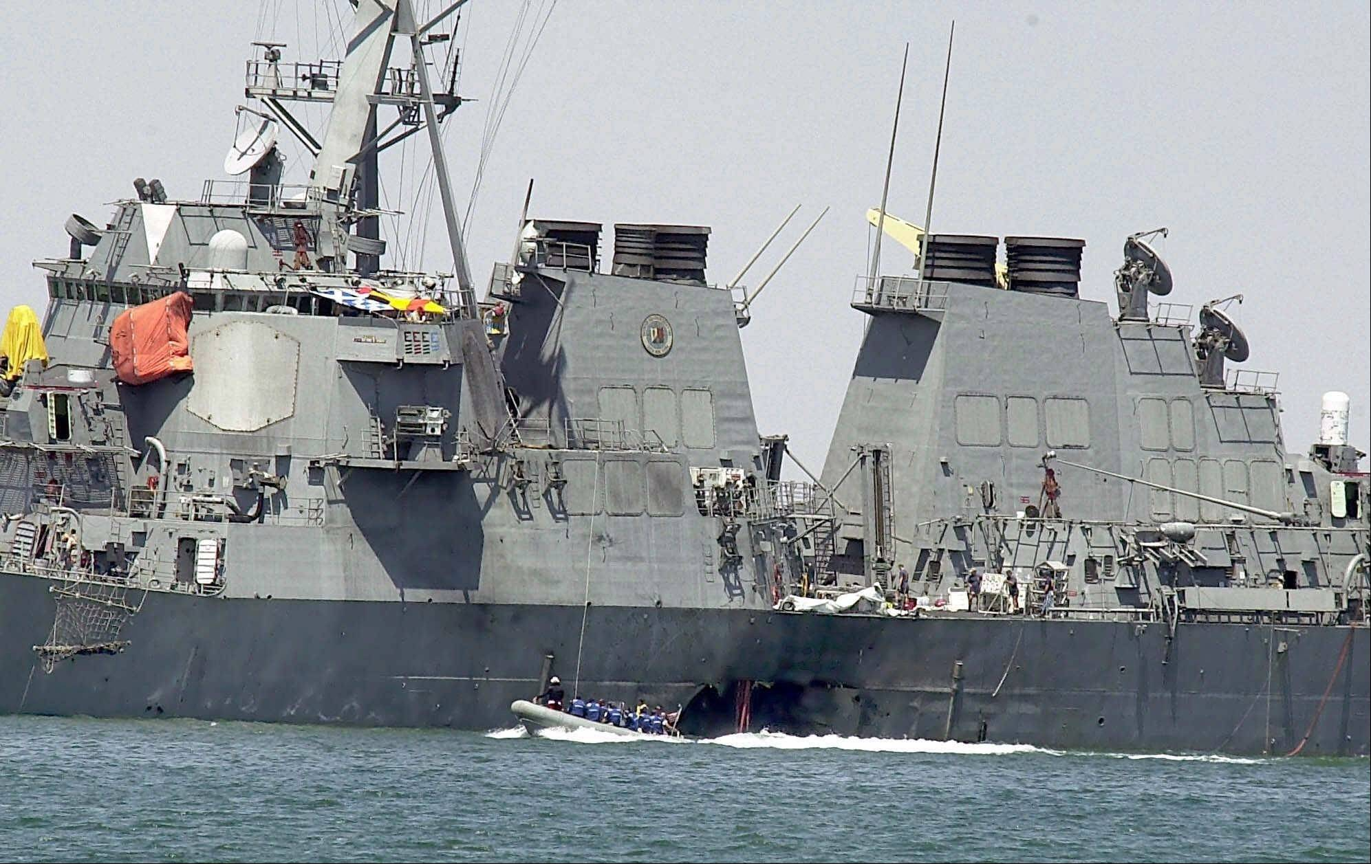 In this Oct. 15, 2000, file photo, investigators in a speed boat examine the hull of the USS Cole at the Yemeni port of Aden, after a powerful explosion ripped a hole in the U.S. Navy destroyer. Abd al-Rahim al-Nashiri, a Saudi national accused in the 2000 bombing of the USS Cole warship, faces trial in a special tribunal for wartime offenses known as a military commission for allegedly orchestrating the bombing of the USS Cole as well as attacks on two other ships. But his lawyers say that since the U.S. wasn't at war at that time, the 47-year-old shouldn't be tried at Guantanamo.