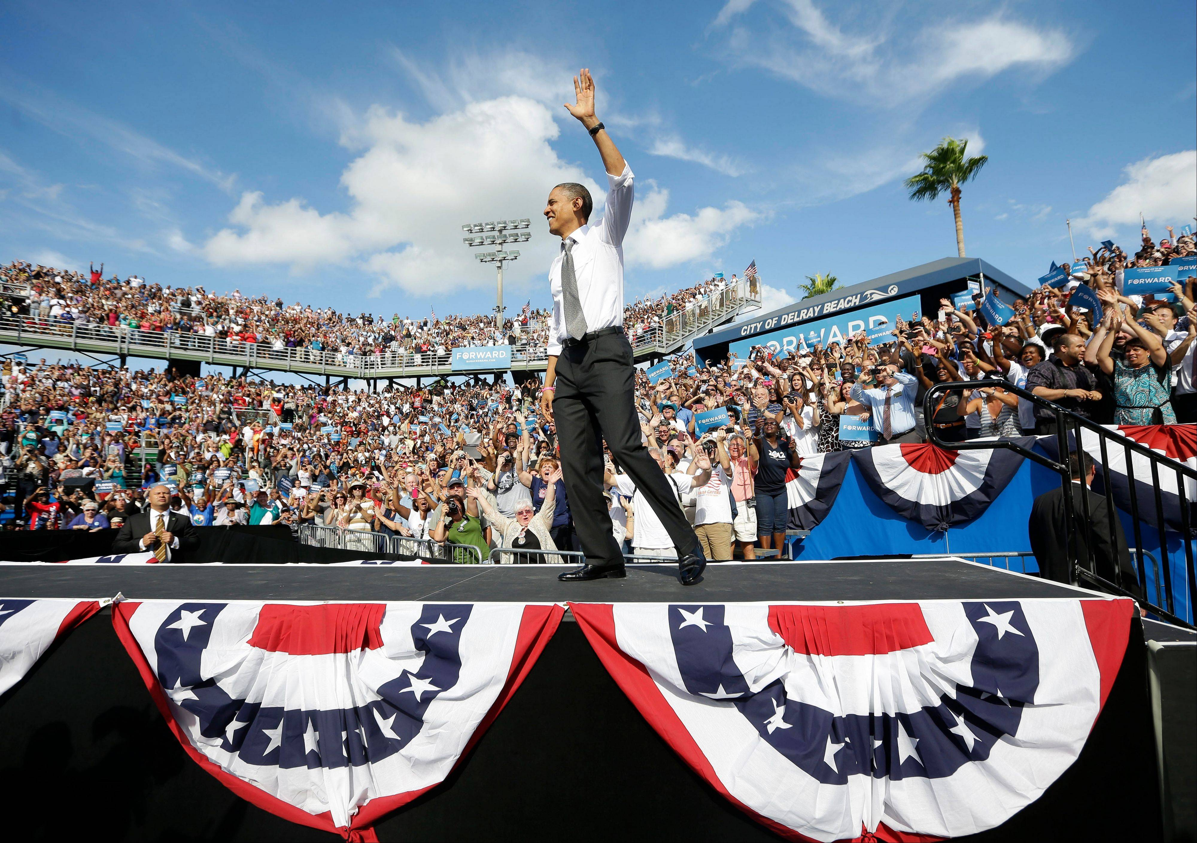 President Barack Obama waves as takes the stage at a campaign event at Delray Beach Tennis Center, Tuesday in Delray Beach, Fla.