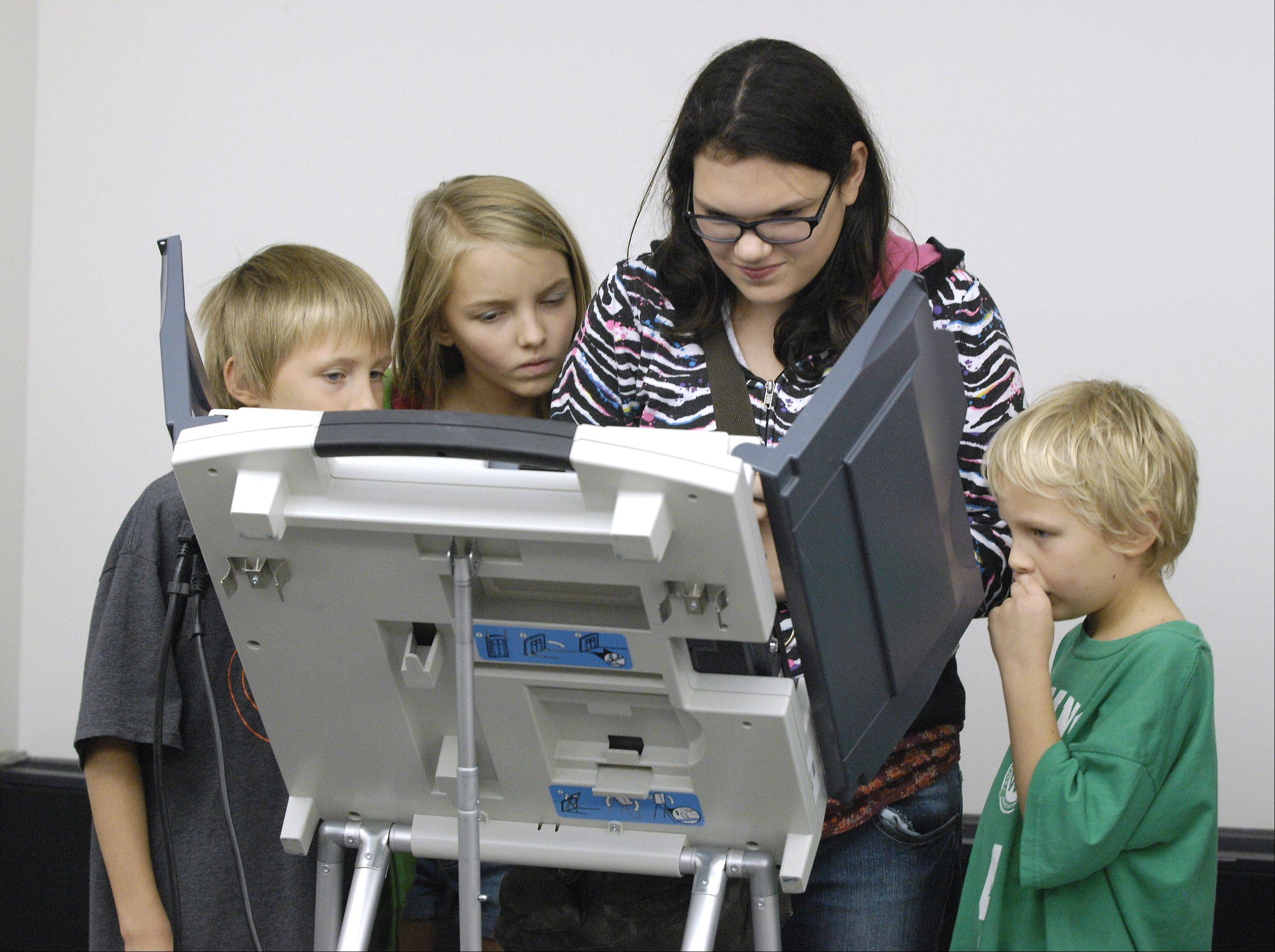 Lydia Penosky, 21, of Wheaton votes for the first time with some of her bothers and sisters at her side, Daniel, 9, Liberty, 11, and Patrick, 7, on the first day of early voting at the DuPage County government building in Wheaton. As of 2:30 p.m. more than 334 DuPage County residents had voted at the government building location.